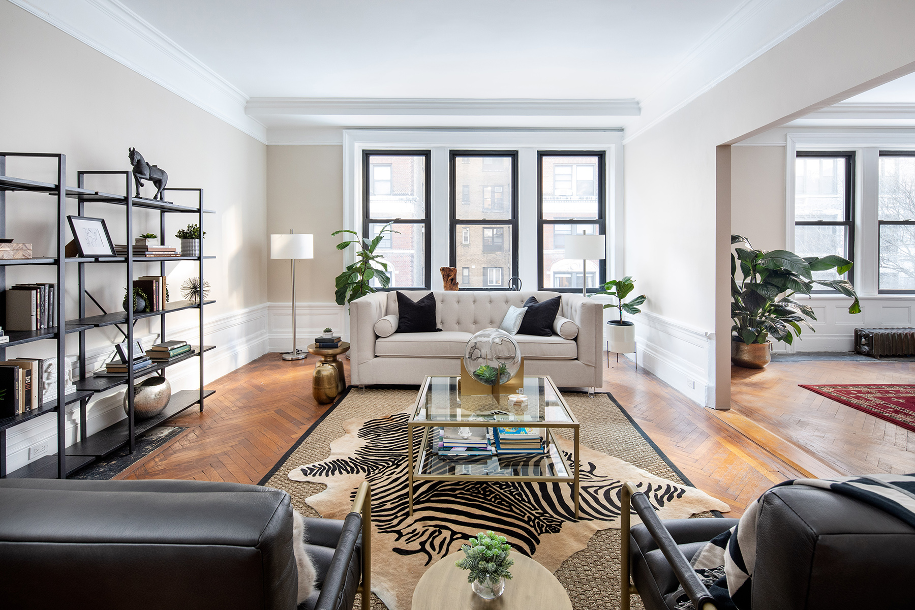 A living room with three windows, a beige couch, a large rug, a glass coffee table, and two leather chairs.