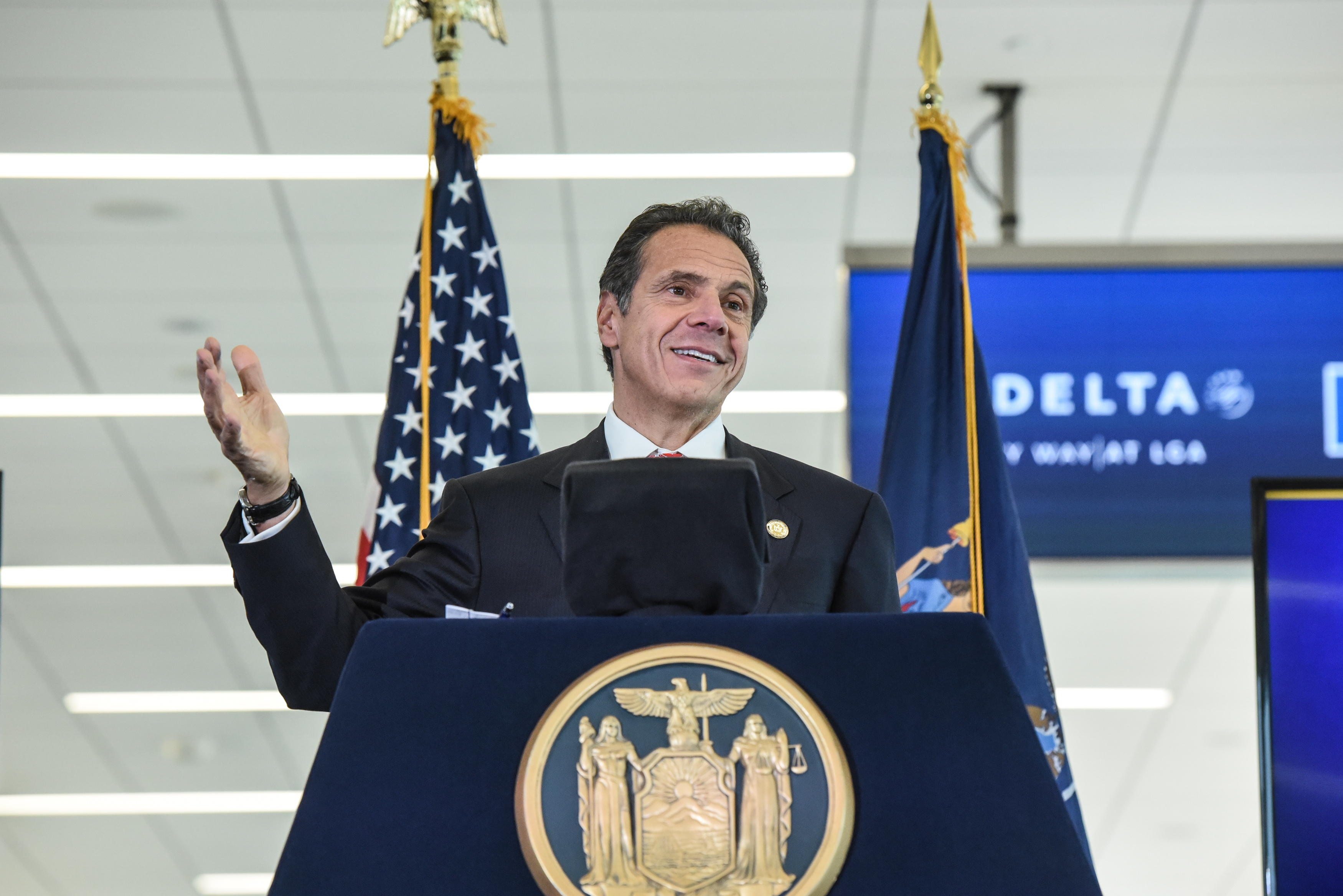 Governor Andrew Cuomo stands behind a podium as he delivers a speech in Queens