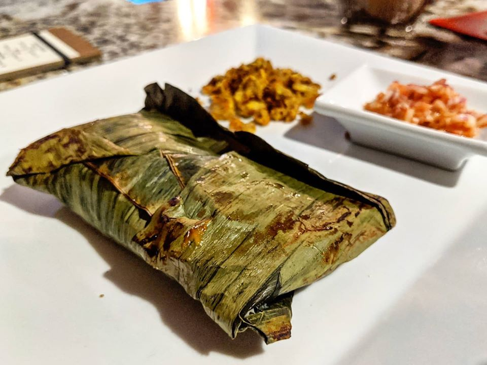 A rectangular packet of banana leaf hides something inside. It's sitting on a white plate, with a couple of side dishes blurred in the background, and the plate is on a marble surface.