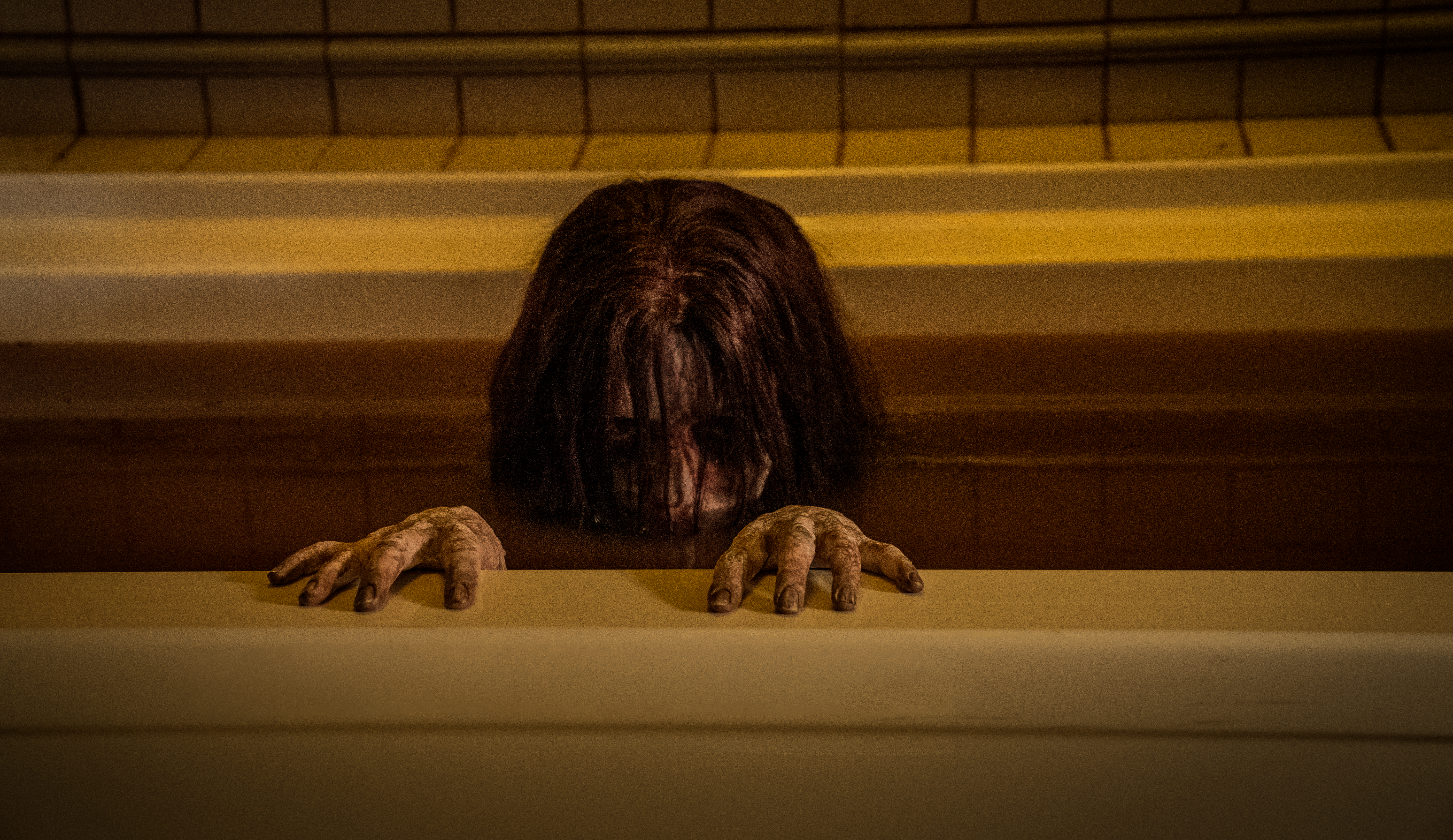 a black-haired girl mostly submerged in red water in a bathtub in The Grudge (2020)