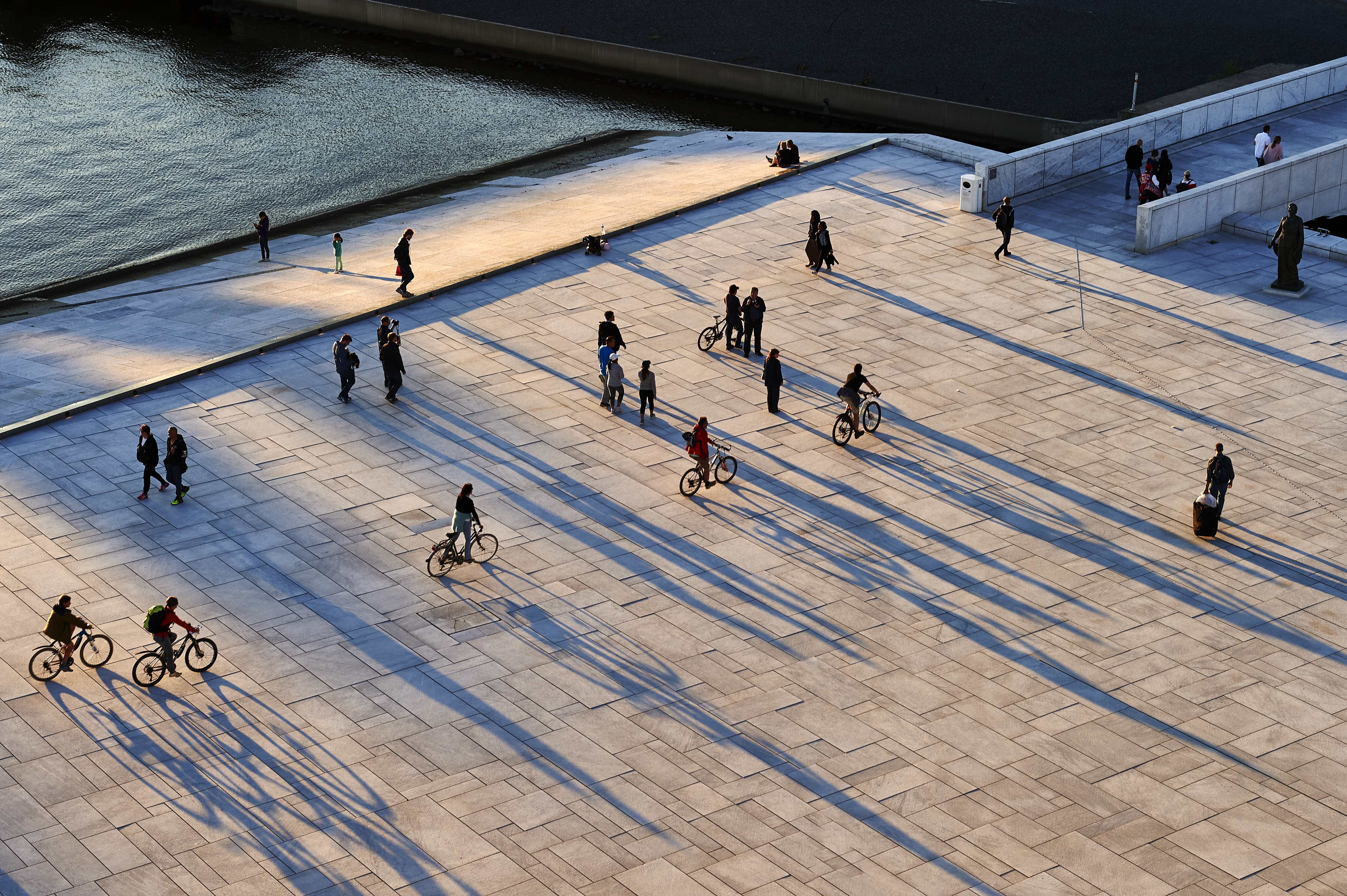 People walk and bike across a sweeping white plaza with dramatic shadows cast against the stone.