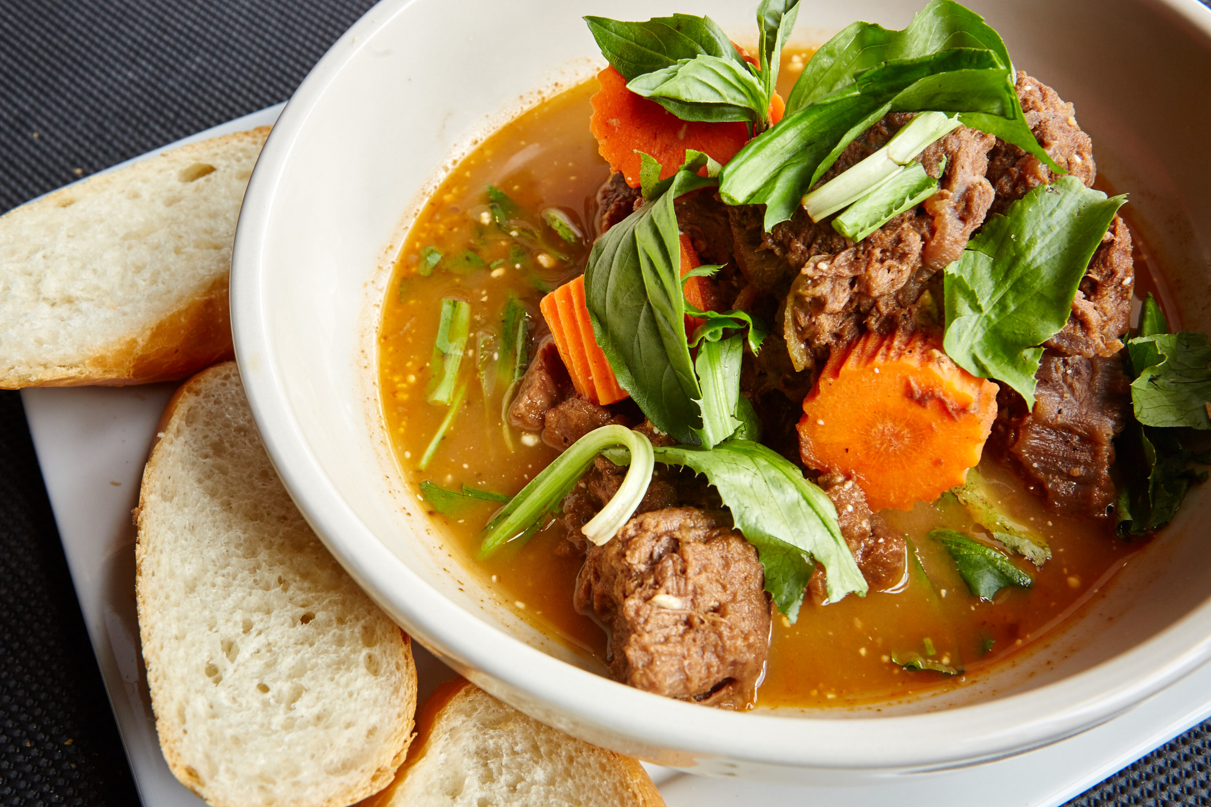 A closeup of a hearty beef pho at Coba Viet Kitchen and Ales, with a side of bread.