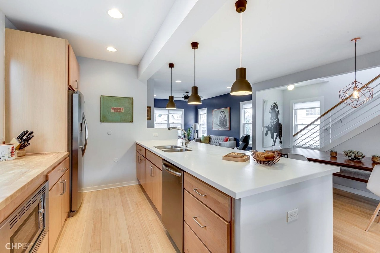 A contemporary kitchen with white countertops and wood cabinets. There are light hardwood floors and industrial style pendant accent lights.