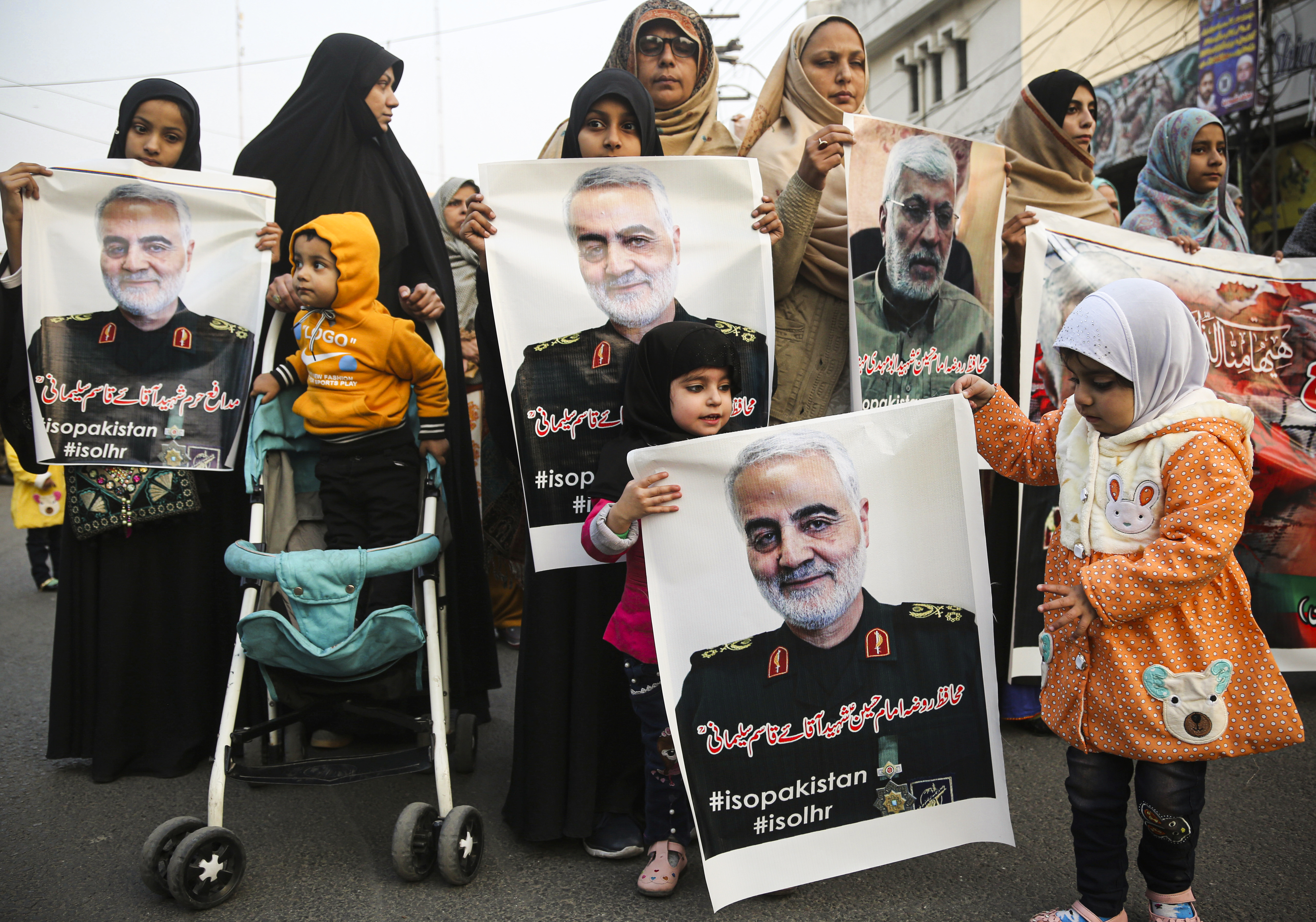 At a protest in Pakistan, women and children hold posters and signs depicting Qassem Soleimani, the Iranian military leader killed in a US airstrike in Iraq.