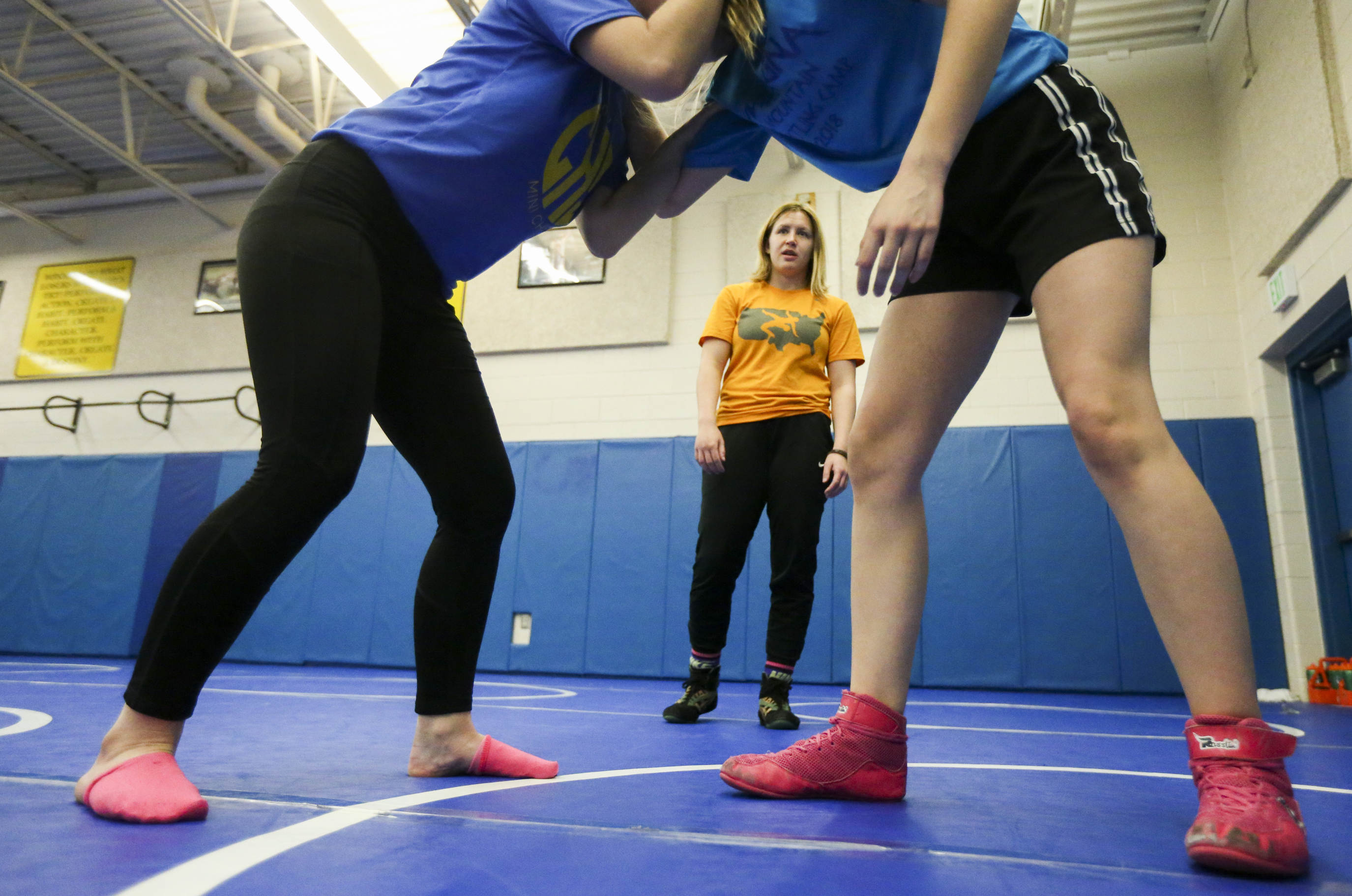 Cyprus High School girls wrestling coach Cara Romeike, center, watches Destinee Cummings, 14, left, and Cheyenne Cummings, 15, work on a move at the Magna school on Wednesday, Nov. 20, 2019.