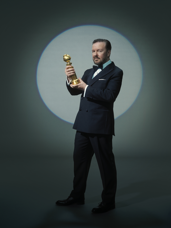 Host Ricky Gervais holding a Golden Globe Award statue.