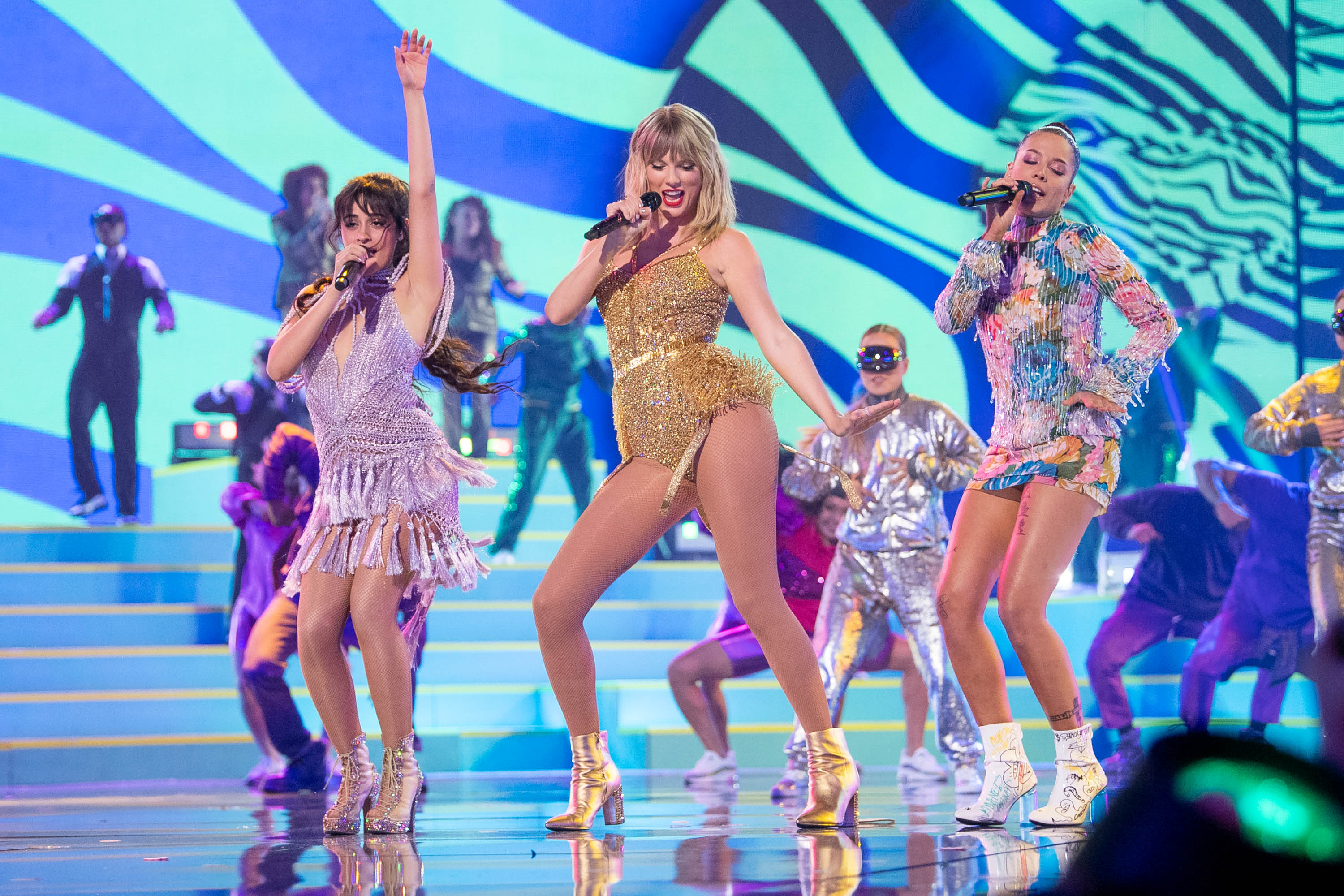 Taylor Swift on stage at the 2019 AMAs surrounded by other performers and dancers.