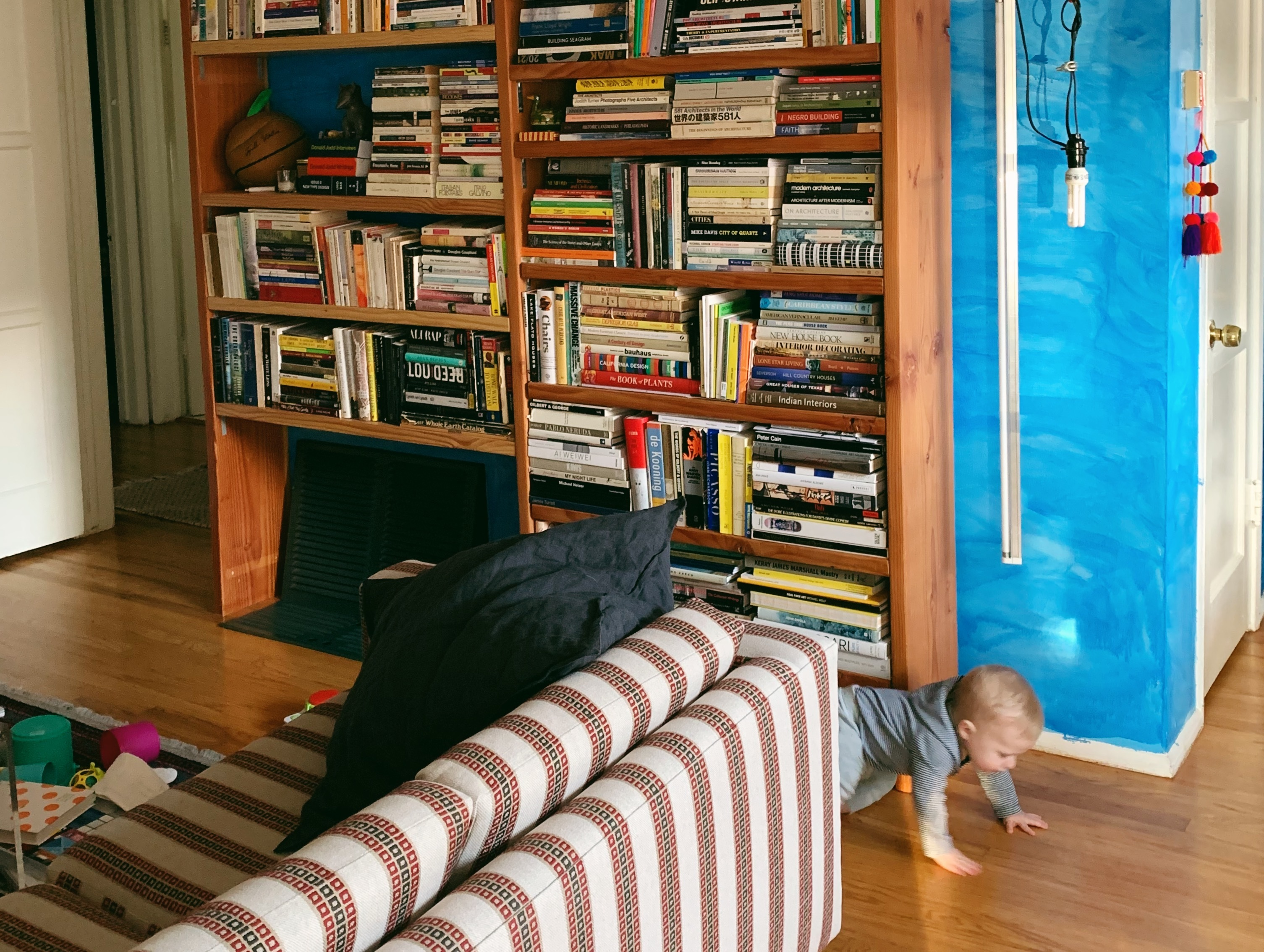 A toddler boy crawls across a wood floor. To his left is a large bookcase against a light blue-painted wall. To his right, a striped couch.