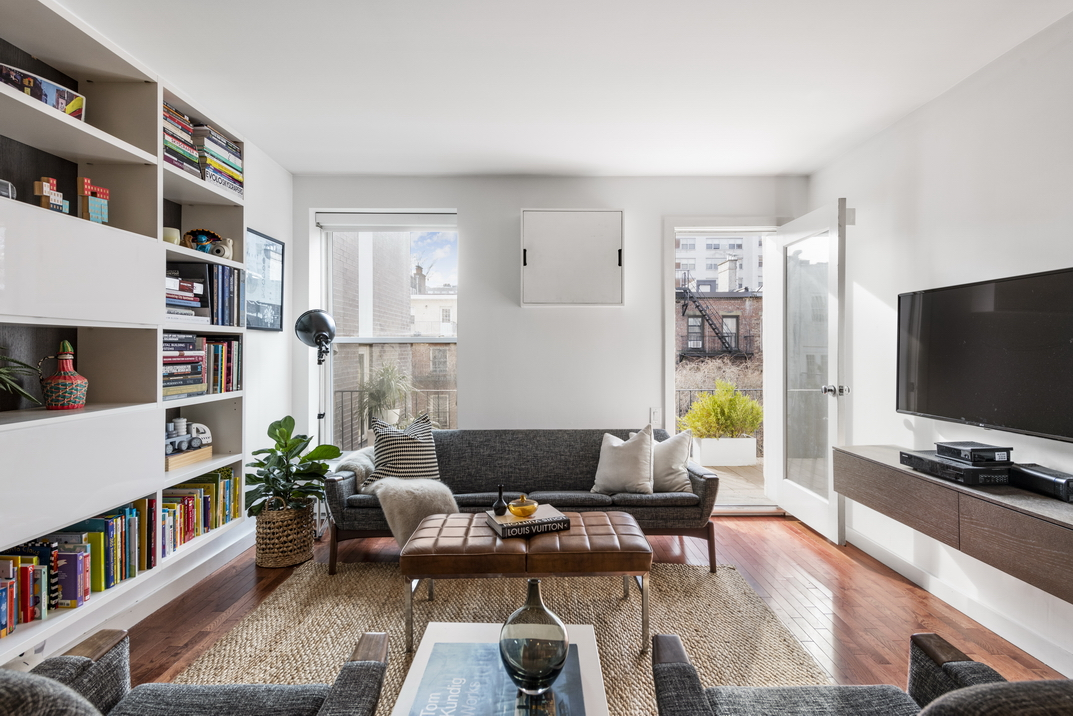 A living room with a dark grey couch, hardwood floors, a large book shelf, a TV on a stand, white walls, floor-to-ceiling windows, and a door that leads to a balcony.