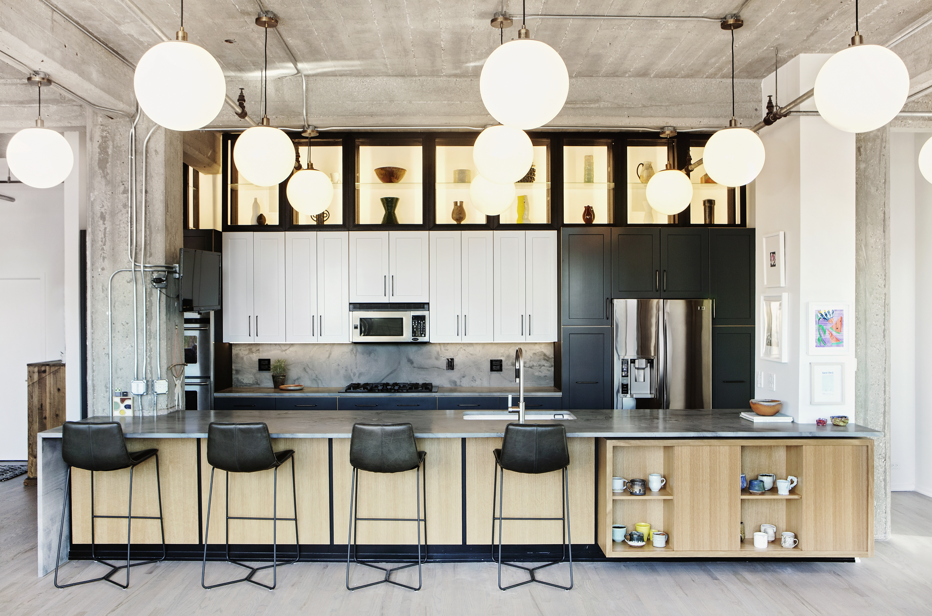 There is a kitchen island made of wood, with a wall of cabinets behind it. A high shelf above the cabinets displays a collection of objects. There is a large table with black chairs. There are many round light fixtures hanging from the ceiling.