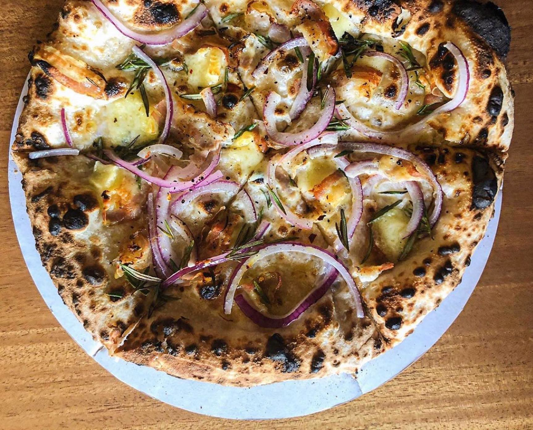 A blistered pizza on a white plate with red onions.
