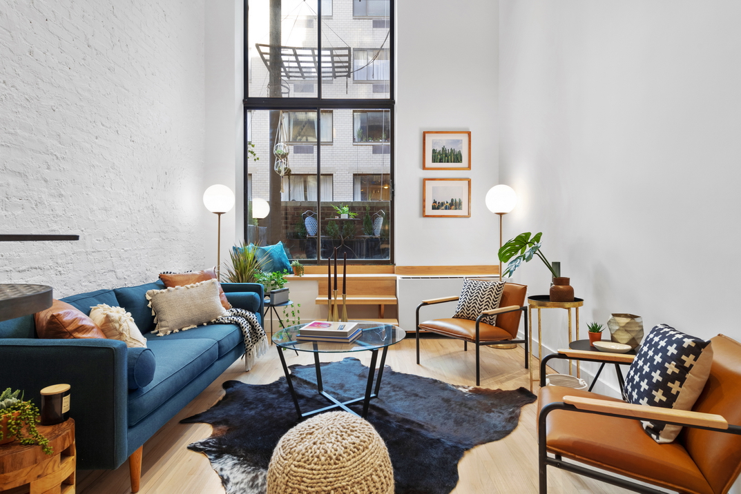 A living area with a blue couch, a large sliding door leading to a balcony, and a glass coffee table in the middle.