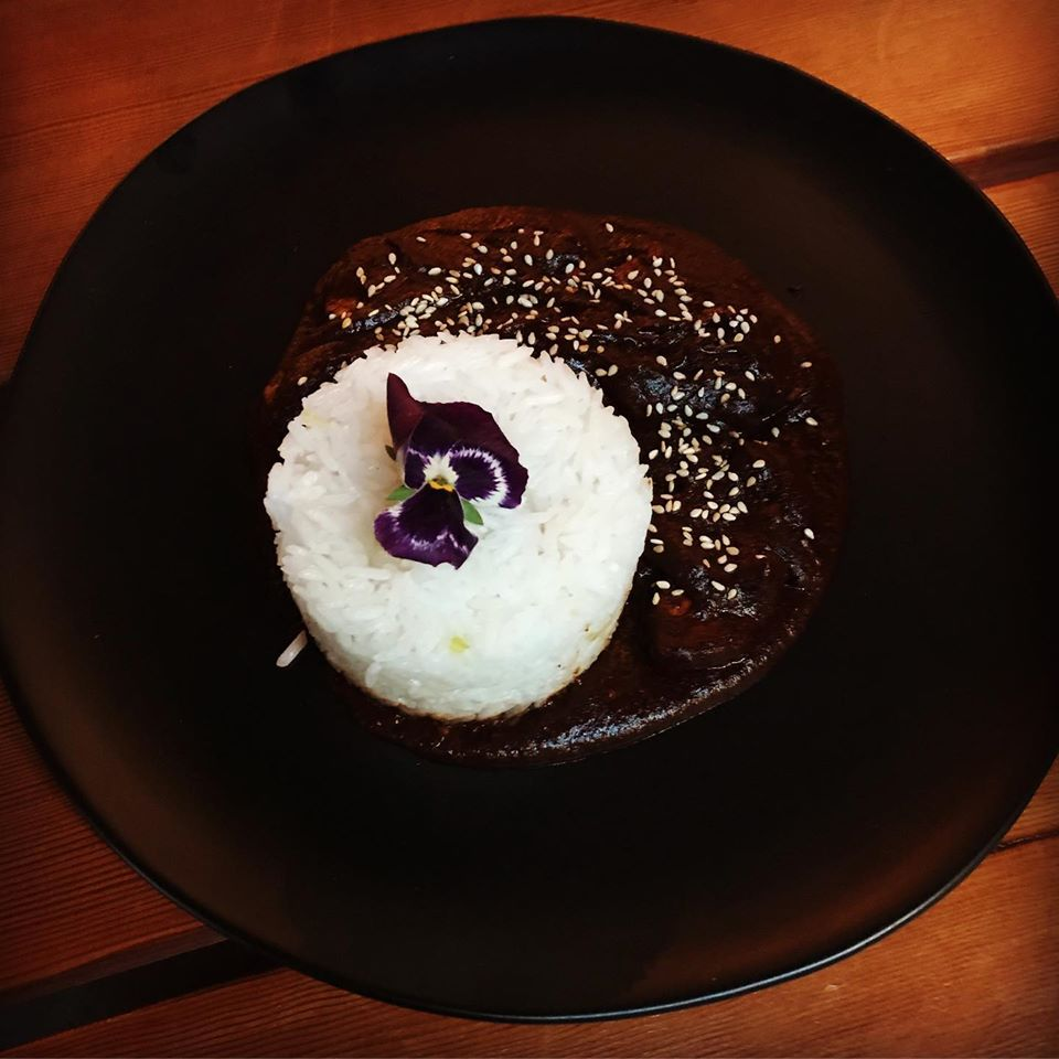 Rice sits in a mound over a dark sauce, topped with an edible flower.