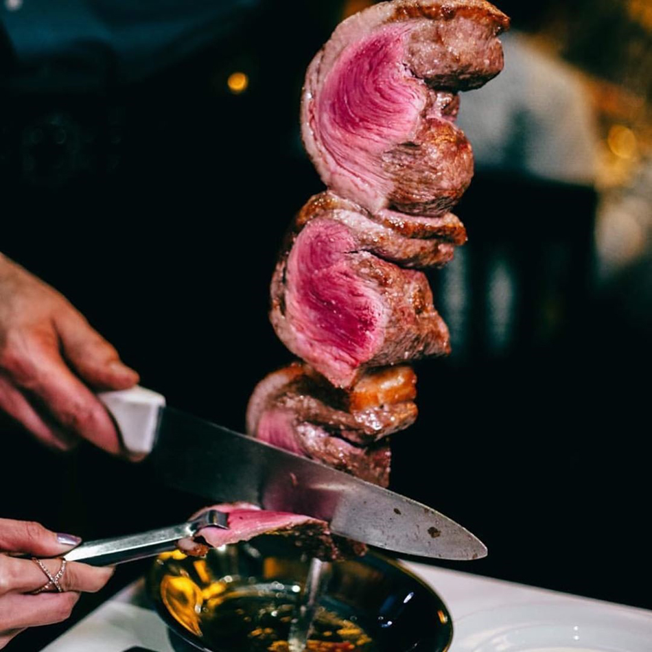 Slicing a serving of grilled meat at Galpao Gaucho Brazilian Steakhouse, coming to the Fashion Show Mall.
