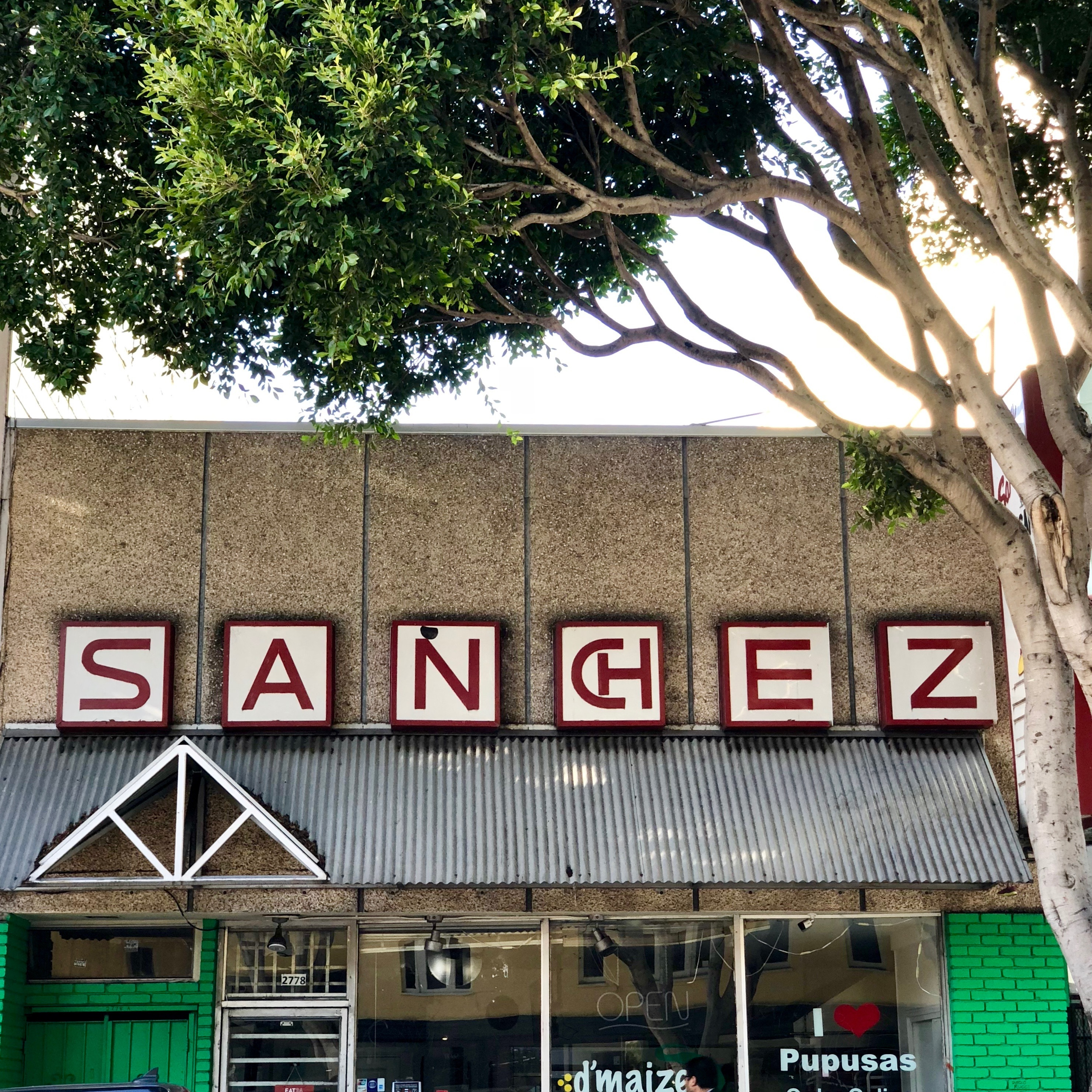 """A tree frames a building facade with a large sign reading """"Sanchez."""""""