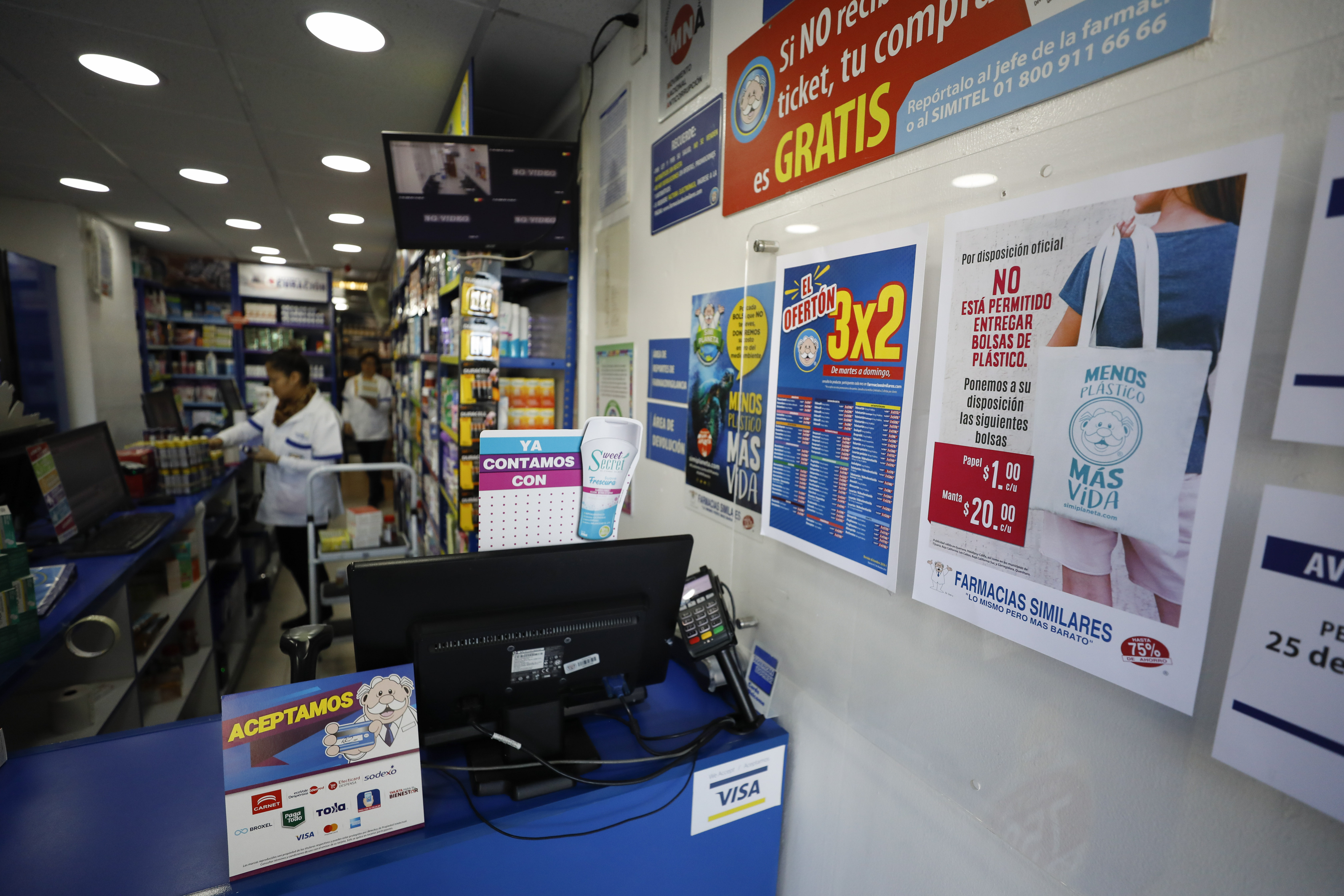 """xA sign posted at a pharmacy reads, in Spanish, """"By official order, it is not permitted to provide plastic bags. We are offering the following bags: Paper, 1 peso [around 5 cents], cotton, 20 pesos [around $1US],"""" in central Mexico City."""