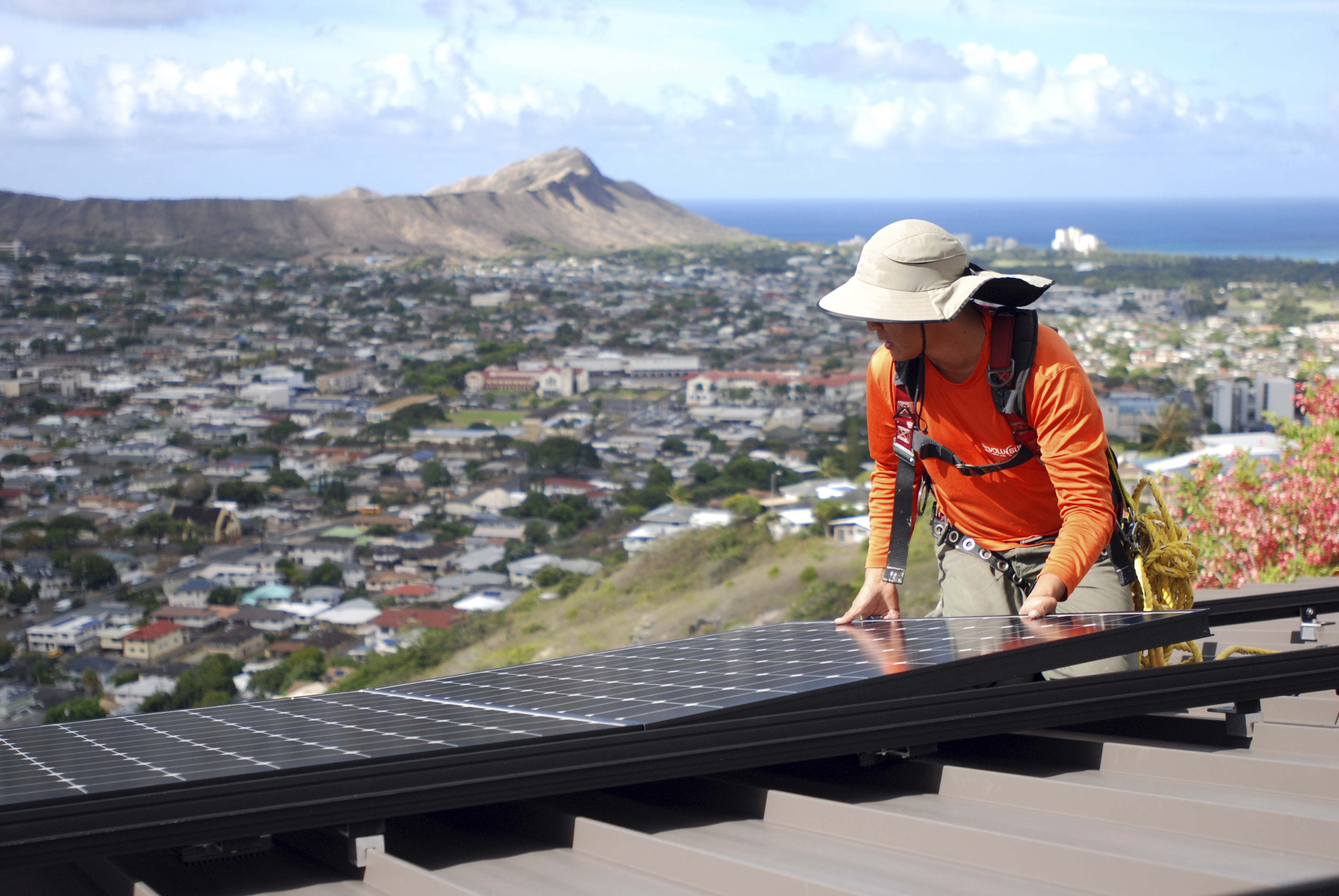 Dane Hew Len, lead installer for RevoluSun, places a solar panel on a roof in Honolulu. If you have the cash, most experts agree buying a solar system outright is a better investment than leasing or taking out a loan.
