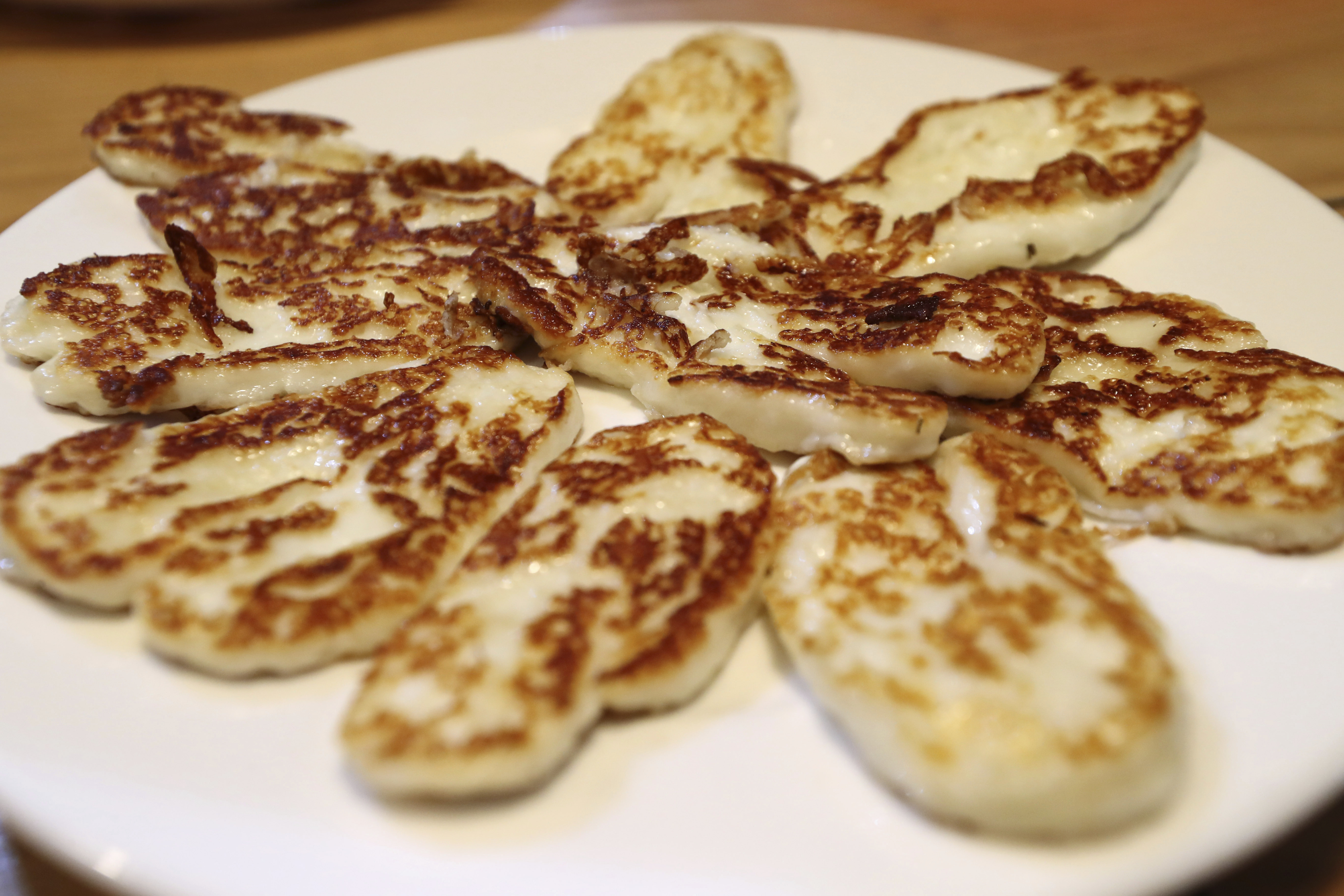 """Cyprus' halloumi cheese is seen roasted on a plate at """"Riverland"""" farm in Kampia village near Nicosia, Cyprus. Cyprus' halloumi cheese, with a tradition dating back some five centuries, is the island nation's leading export."""