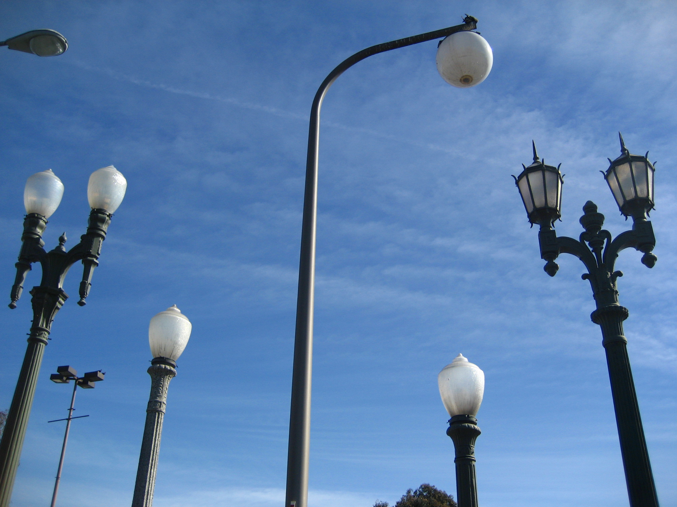 A photo of the tops of streetlights against a background of blue sky.