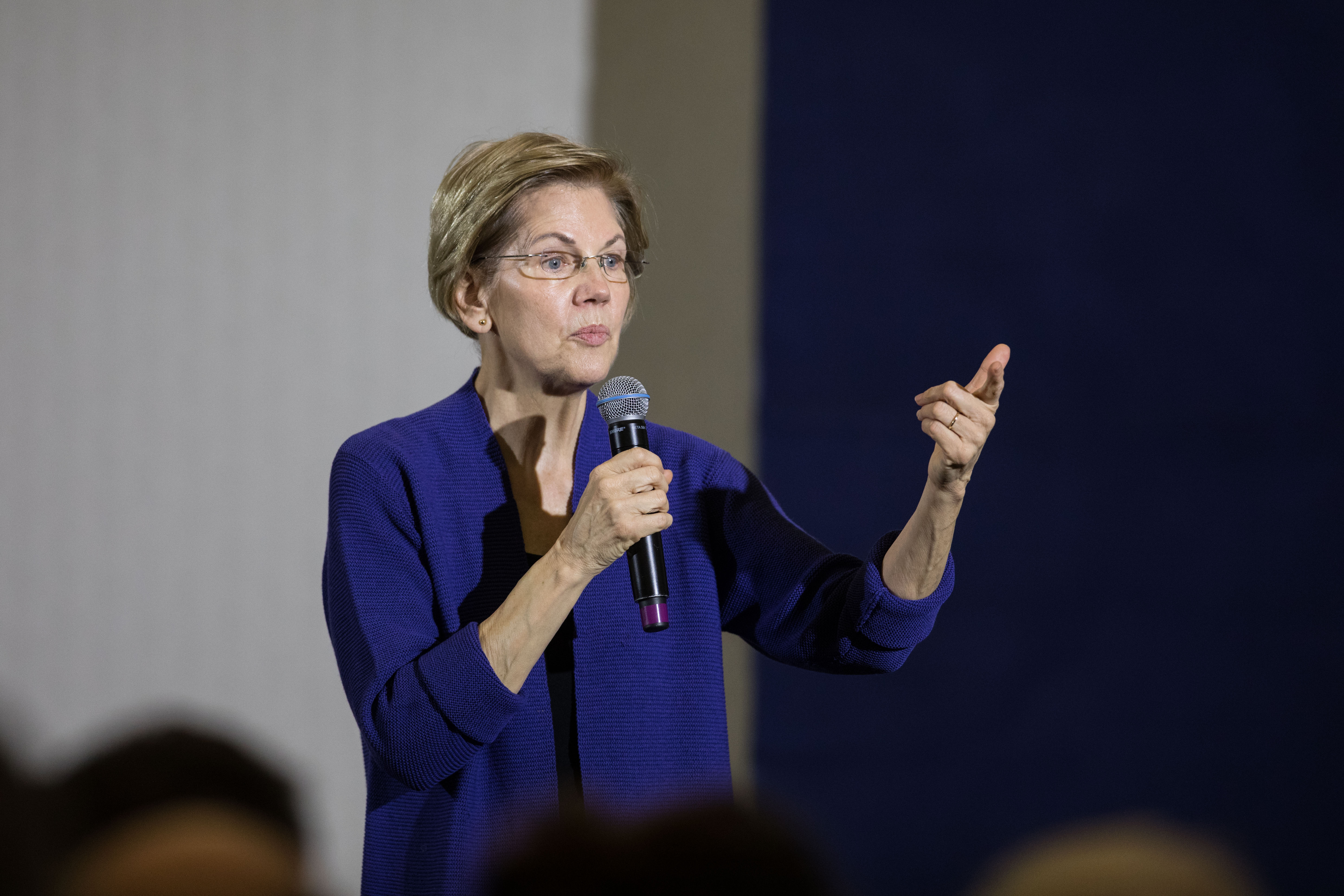 Senator Elizabeth Warren standing and holding a microphone.