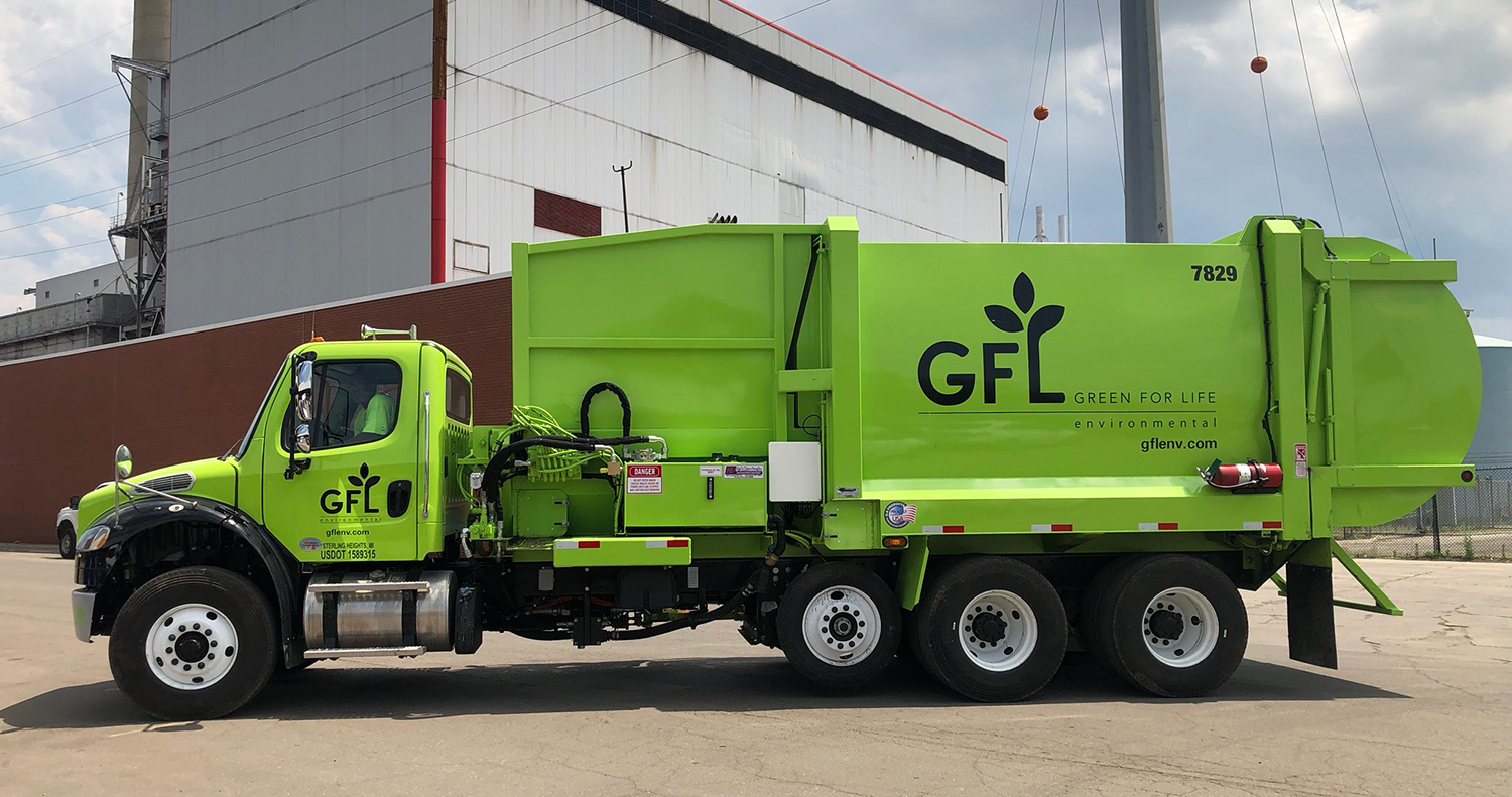 A green truck with GFL, short for Green For Life, written on the side.
