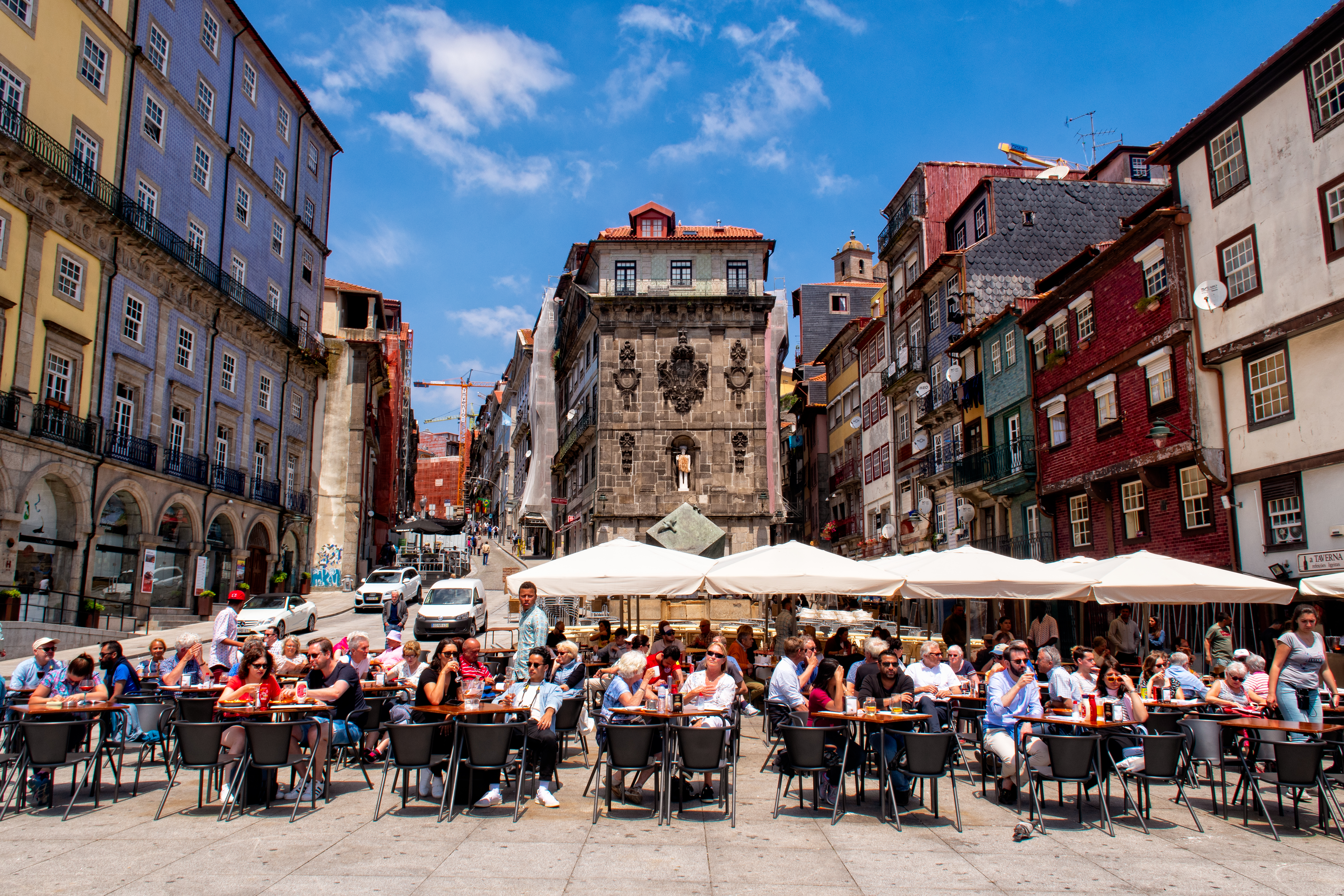 A historic square is packed with diners eating under umbrellas in Porto