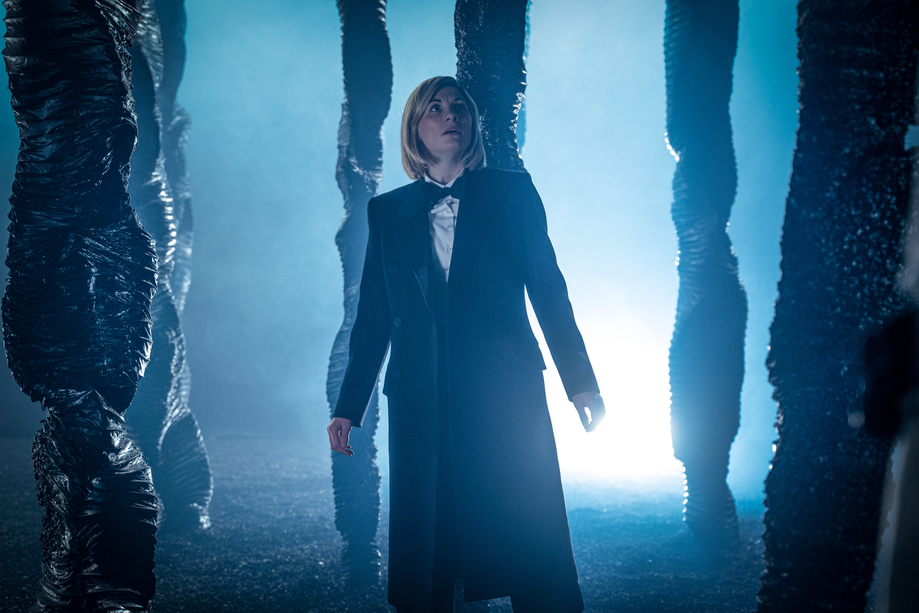 Jodie Whittaker stands in an eerie field of twisted black columns in the 12th season premiere of Doctor Who.