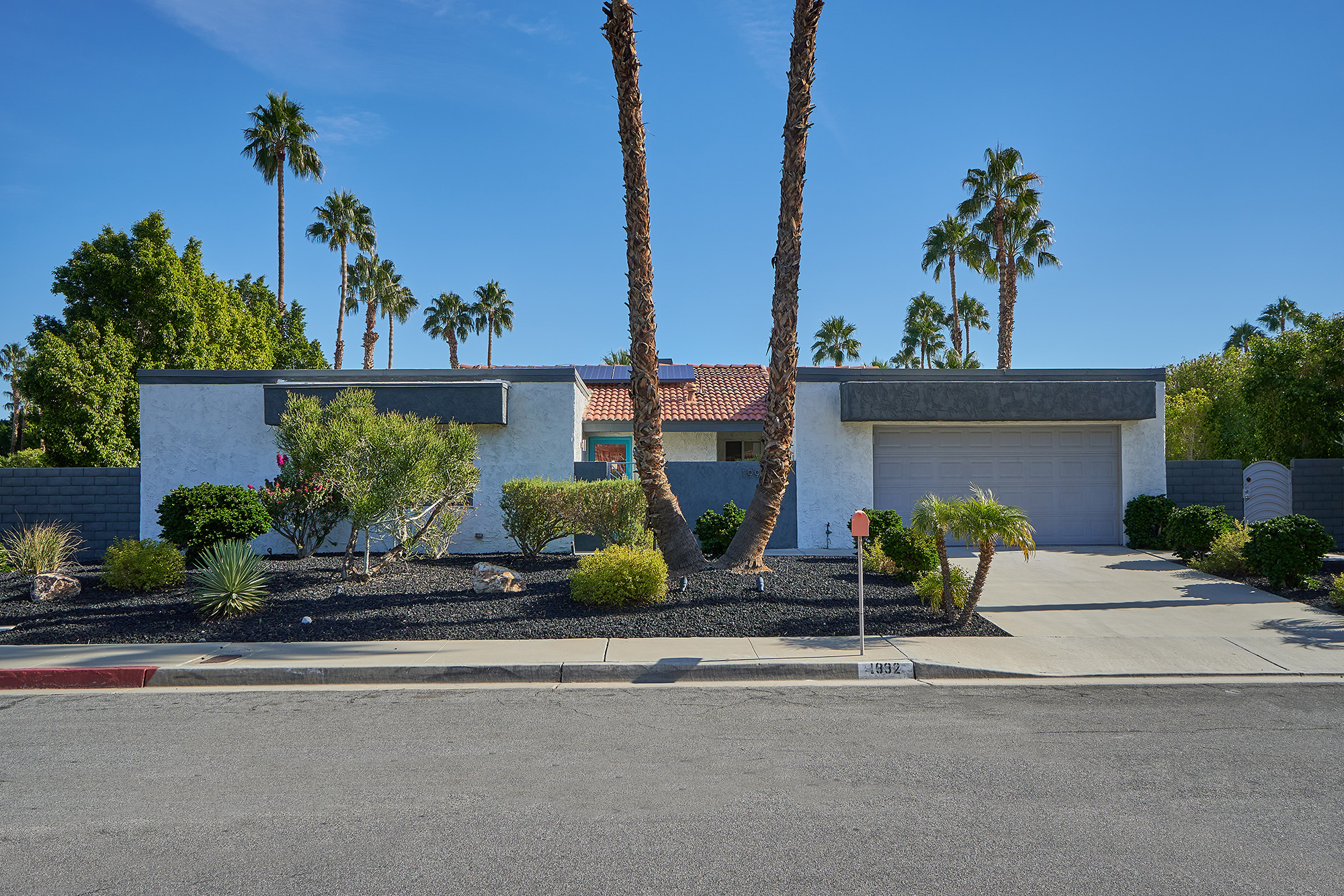 An exterior view of a 1970s home with a paved street in front. The white home has a tiled roof and palm trees surrounding it.