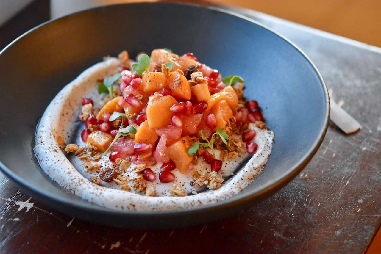 Whipped greek yogurt, housemade vegan granola, persimmon, grapefruit, pomegranate, and wattleseed in a black bowl at Cafe Rowan
