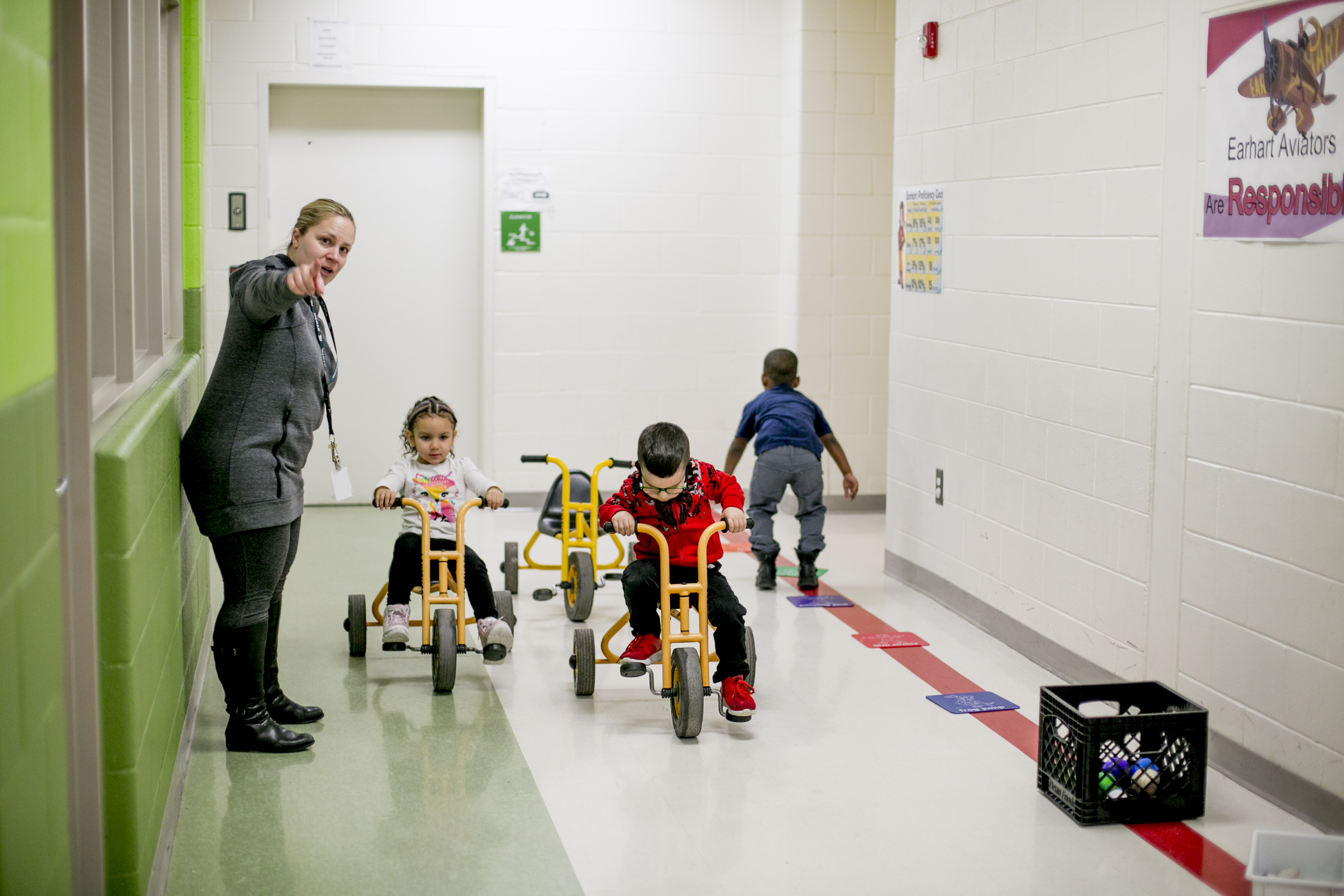 Pre-K students ride tricycles in the halls at Earhart Elementary-Middle school in southwest Detroit.