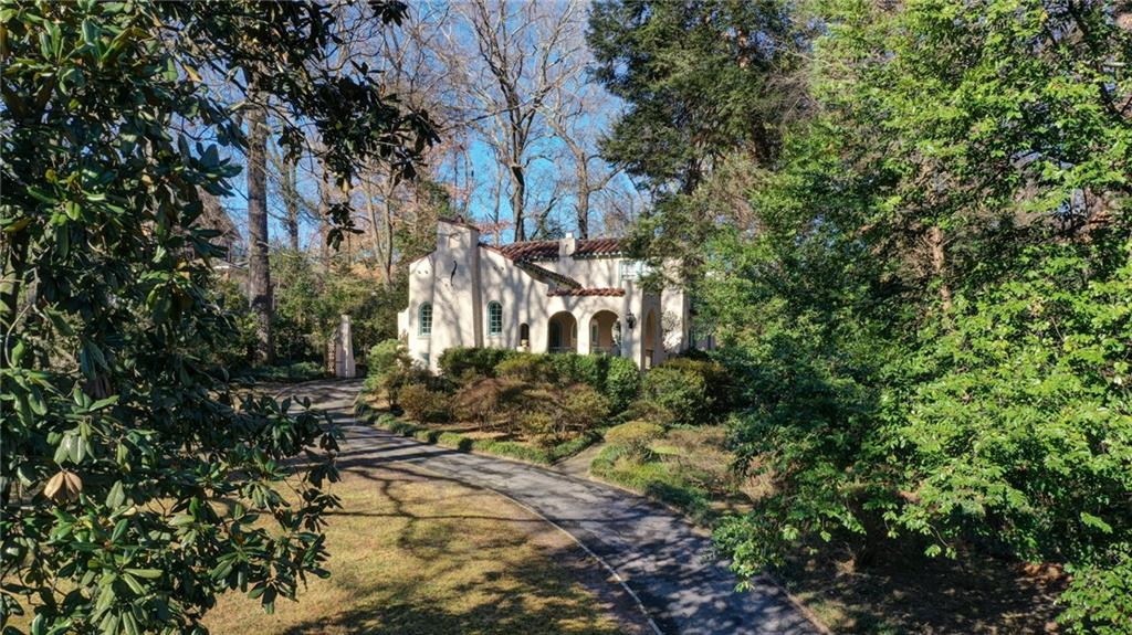 A Mediterranean-style home tucked back on a large lawn with many trees around it.