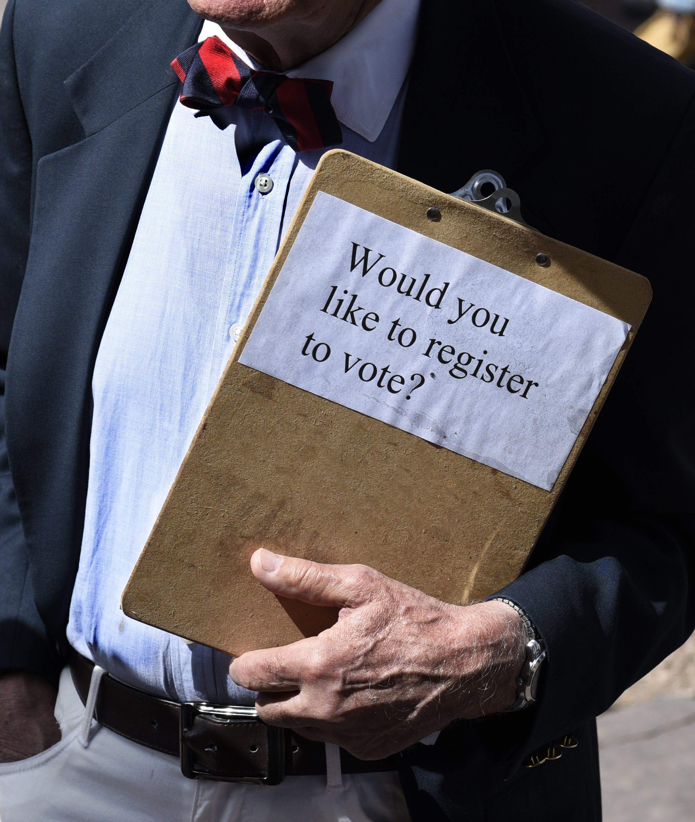 "Man holds a clipboard that reads, ""Would you like to register to vote?"""