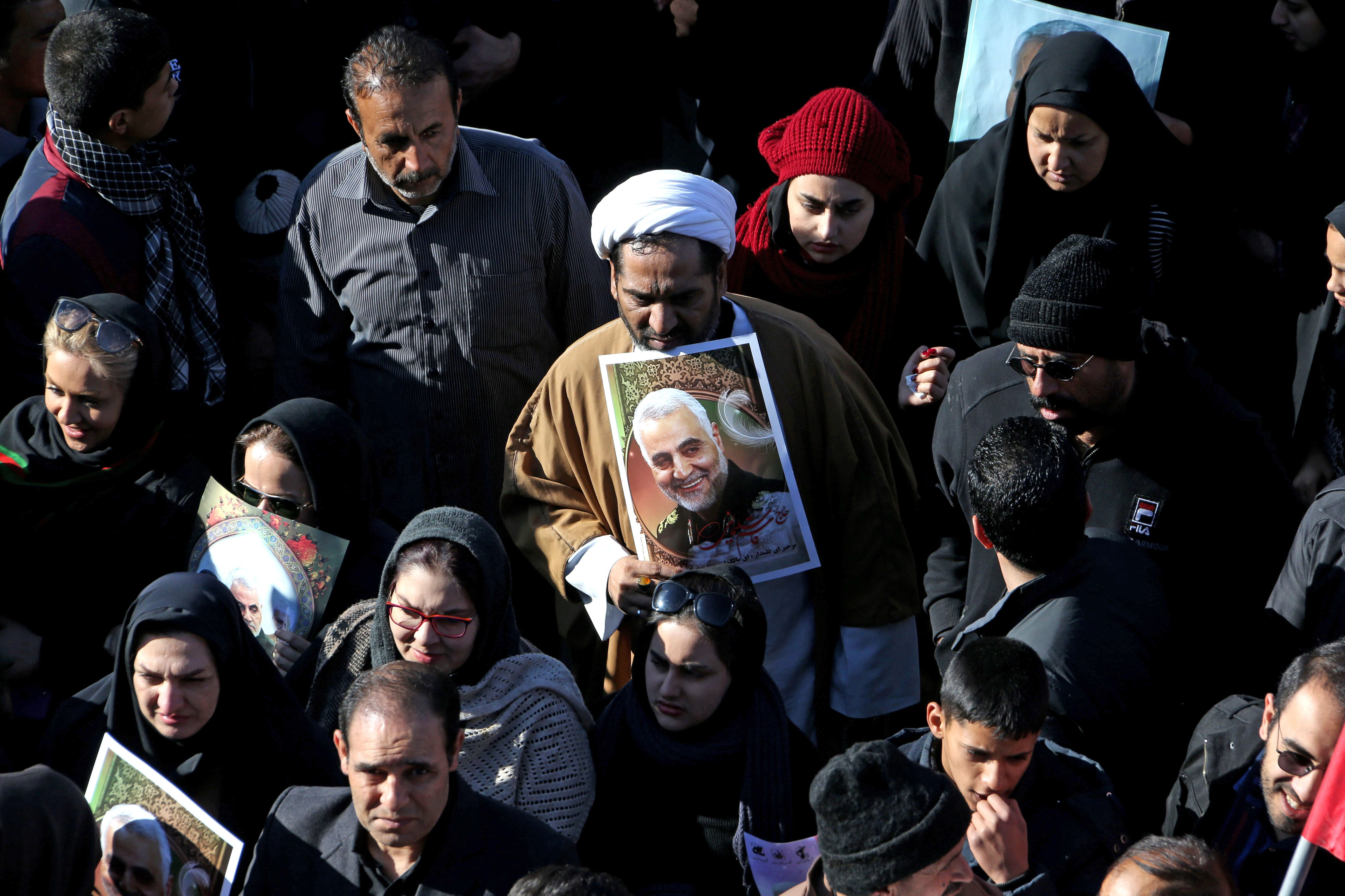 A crowd of Iranian mourners gather around an image of slain top general Qasem Soleimani during his funeral processions in Iran on January 7, 2020.