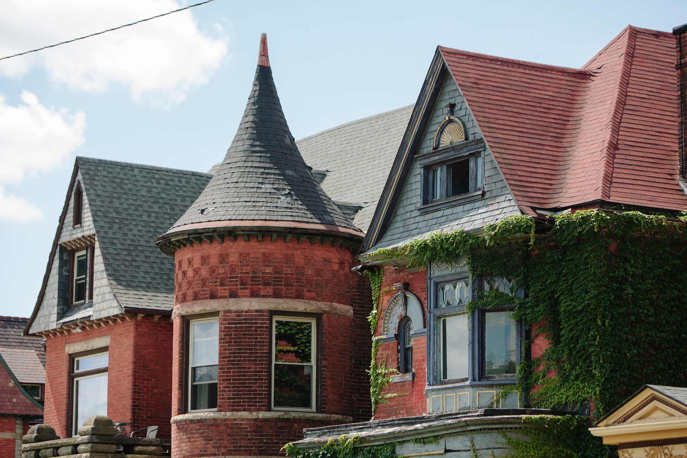 The tops of three homes in Woodbridge. There's the tip of a turret and roofs. Some vines grow outside the windows.