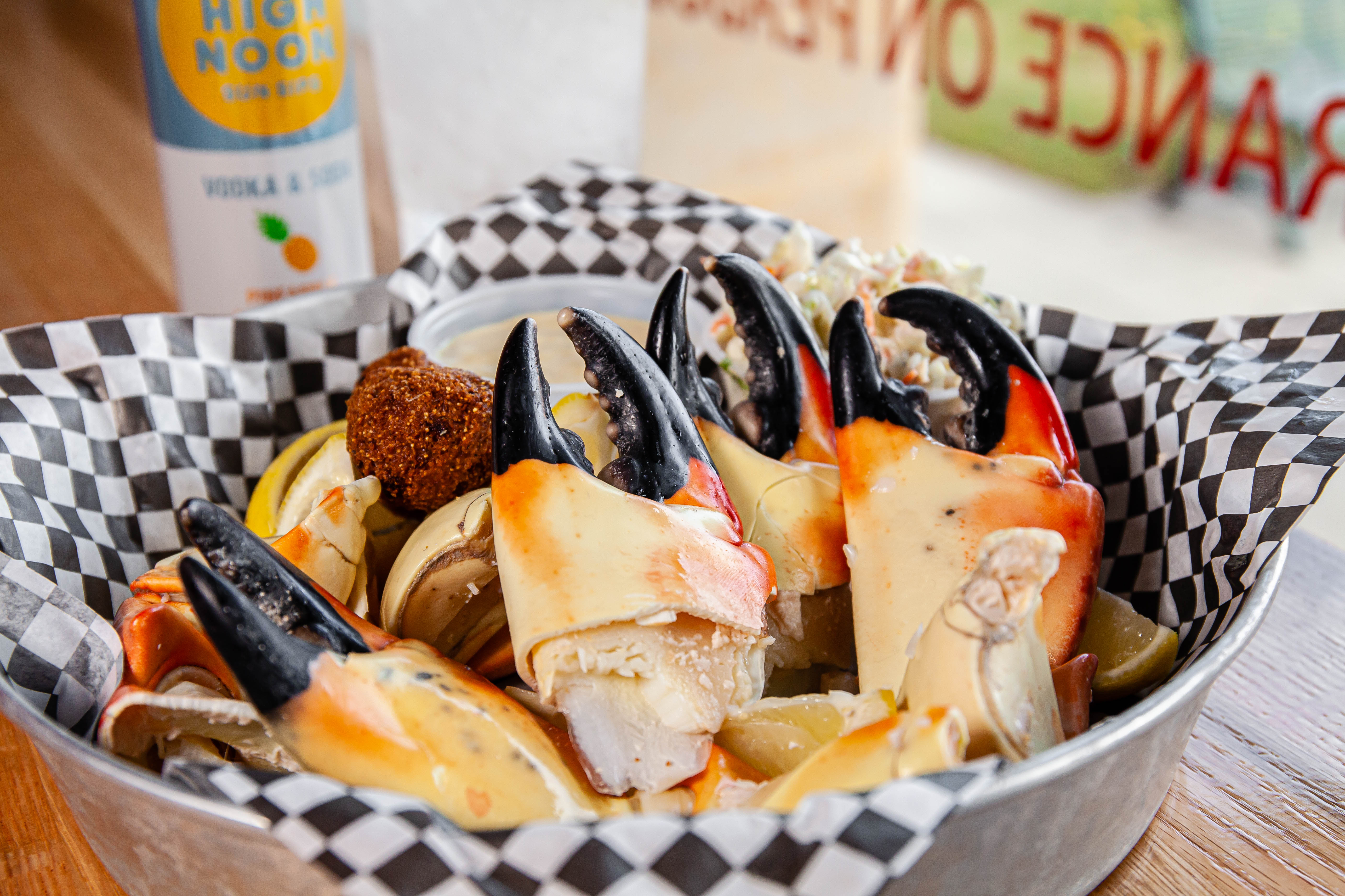 Stone crab claws with black tips arranged in a basket lined with black and white checked paper.