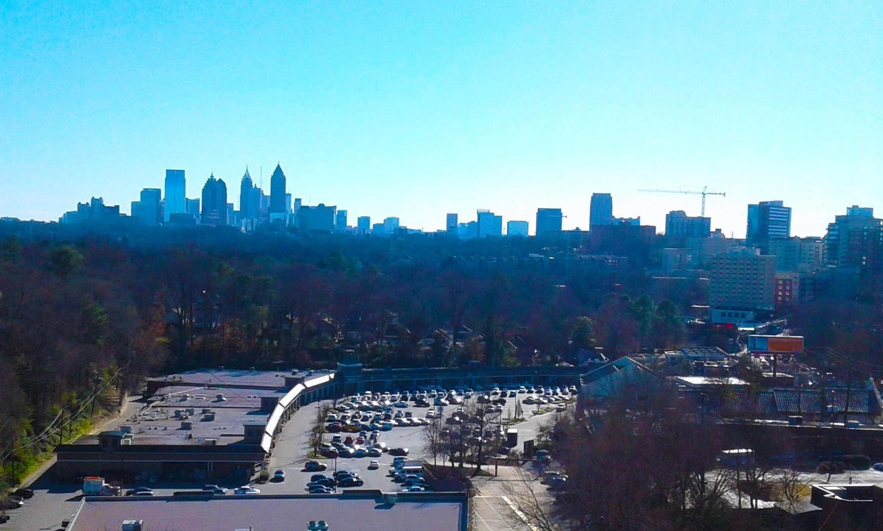 The view with a blue sky across a shopping center to the high-rises of Midtown Atlanta.