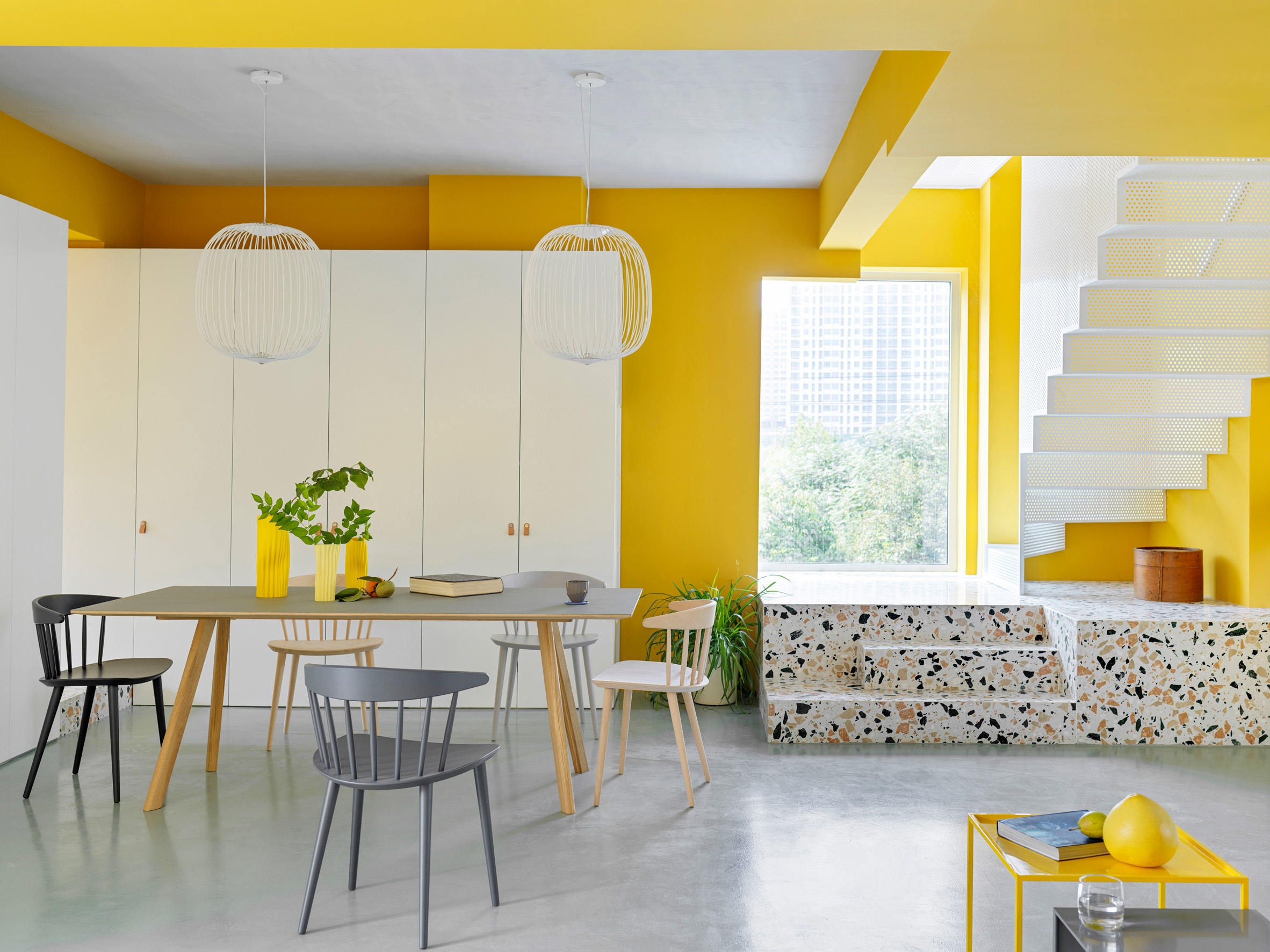 Living room with yellow walls, white furniture, and terrazzo details.