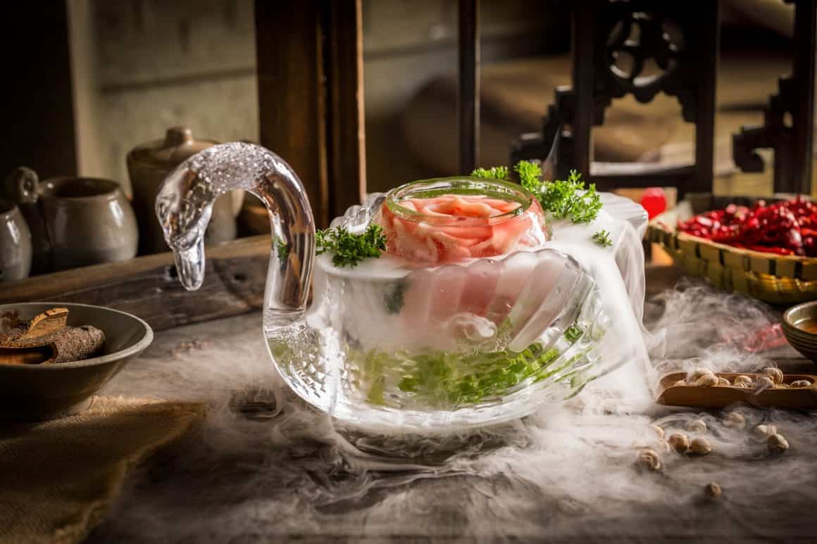 An ornate glass goose sits on a table, surrounded by food and garnishes. The goose doubles as a bowl and is filled with goose intestines.