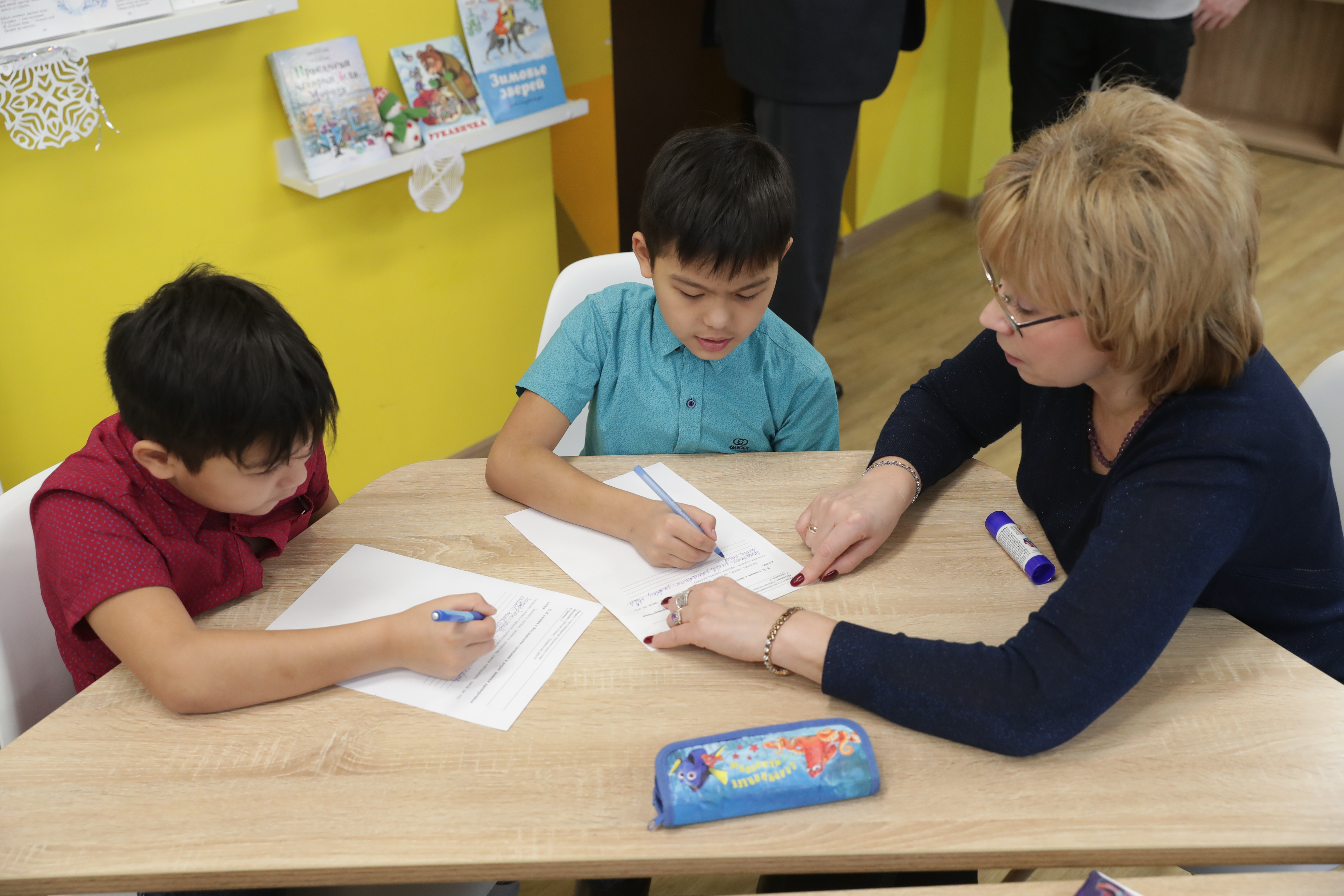 A teacher sits at a work table with two young students.