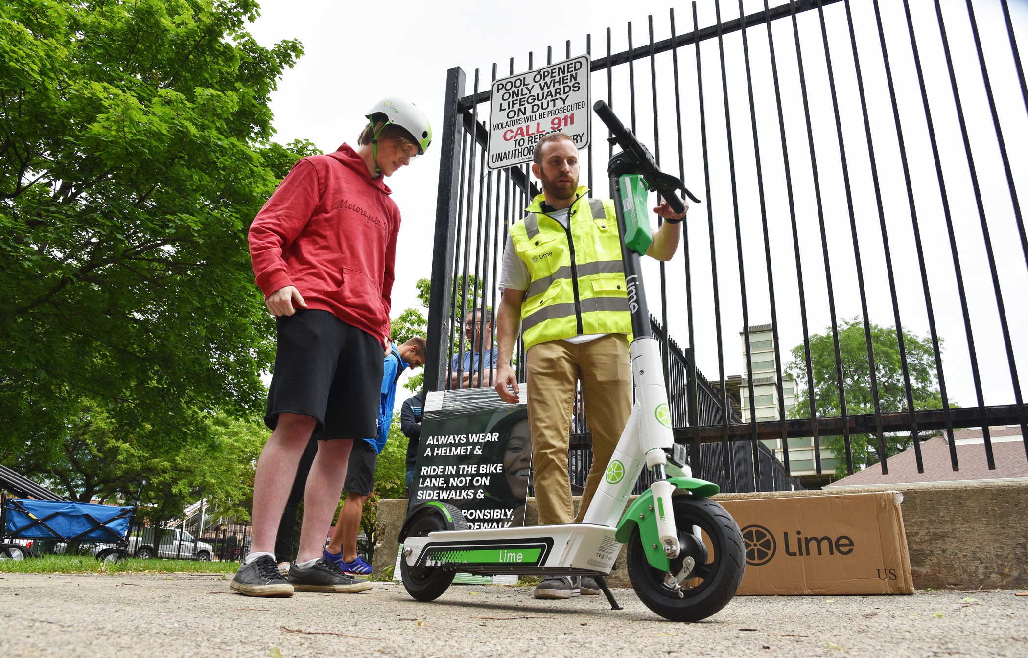 Daniel Chovanec, 21, of Garfield Ridge (left) is shown in June on the day the city's pilot program for dockless e-scooters was launched.