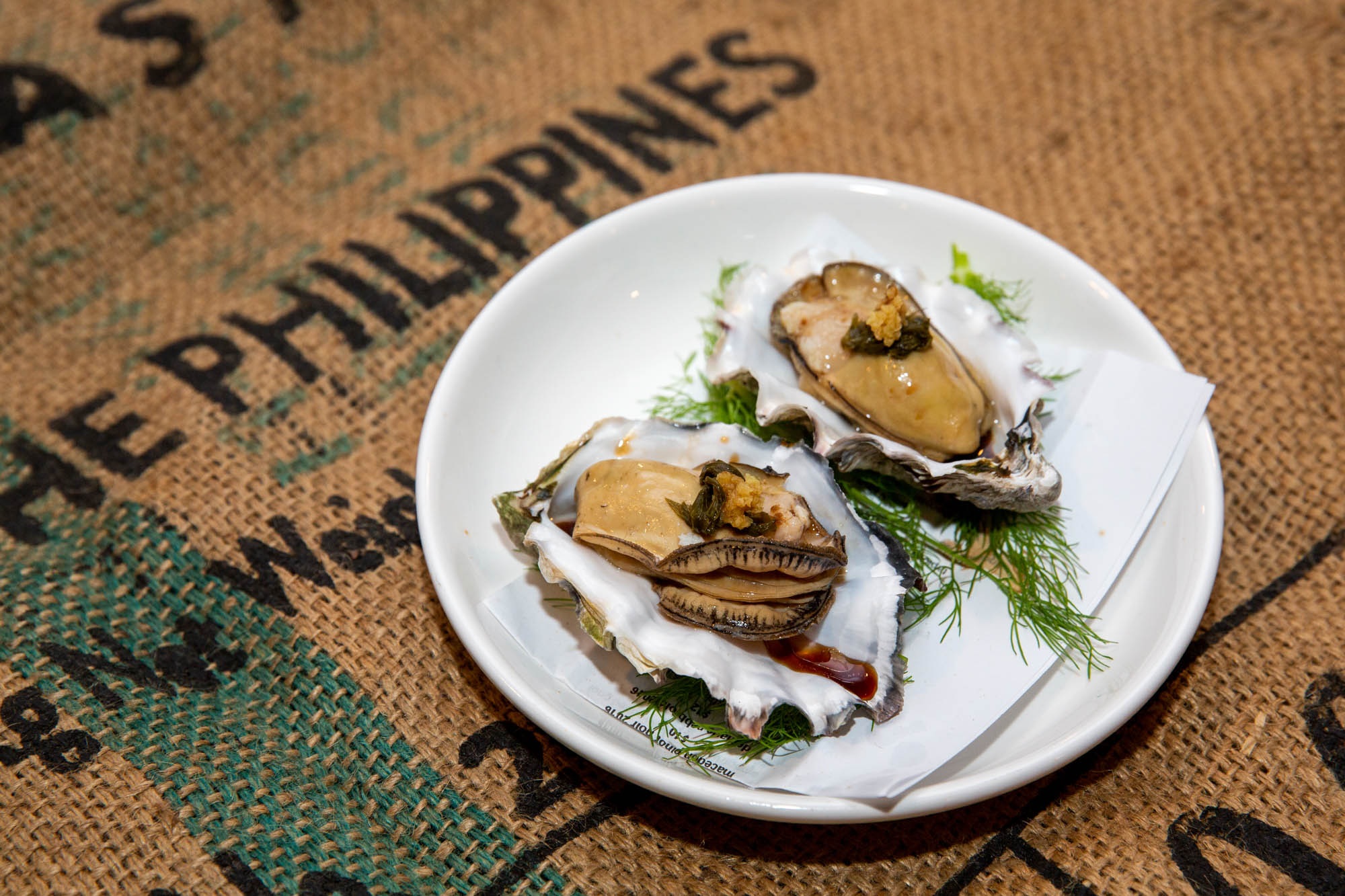 """Smoked oysters with soy-ginger vinaigrette on a burlap sack that says """"The Philippines."""""""