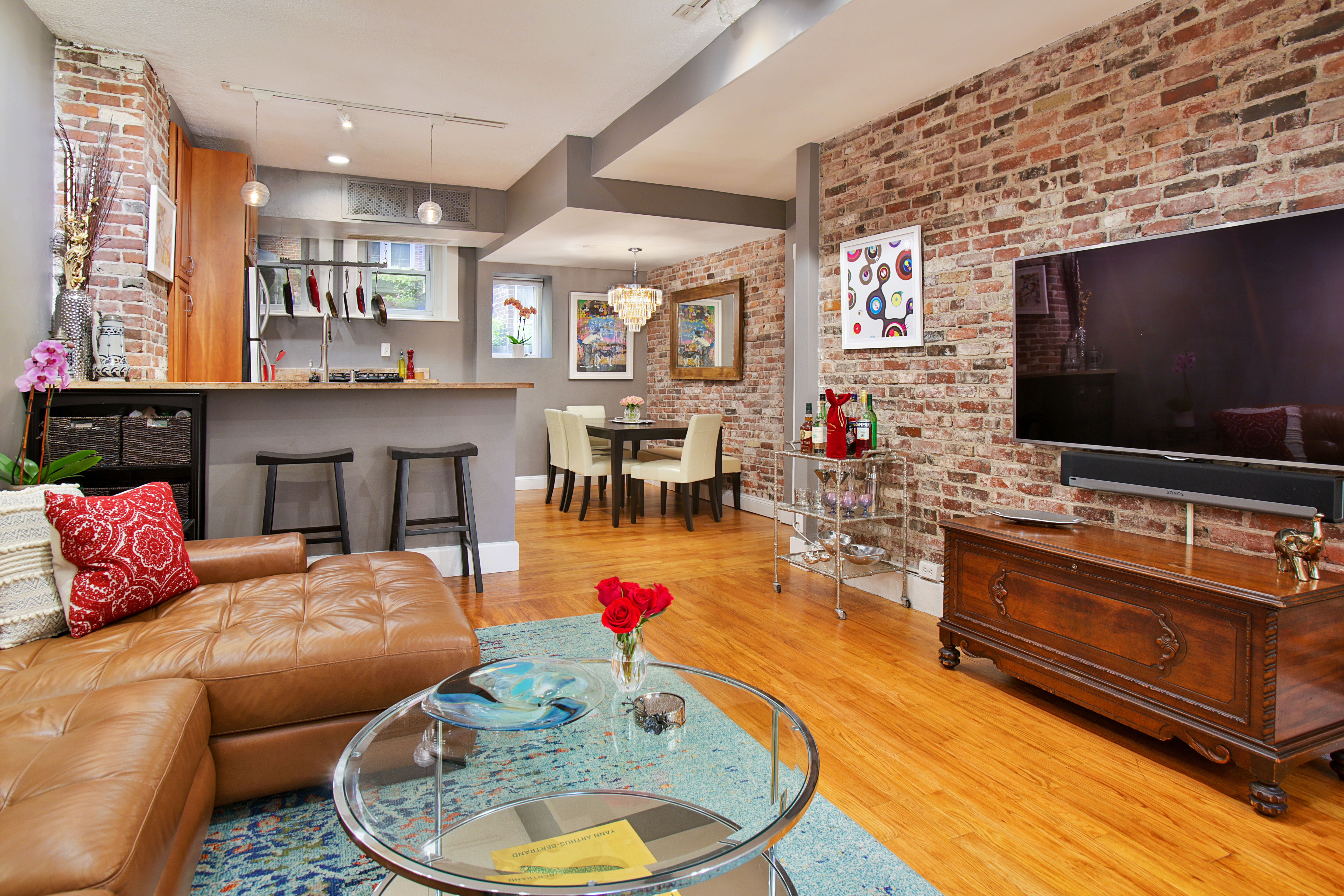 A living room with a large couch facing a TV, and there's a lot of exposed brick on the walls, and the living room leads to a kitchen.