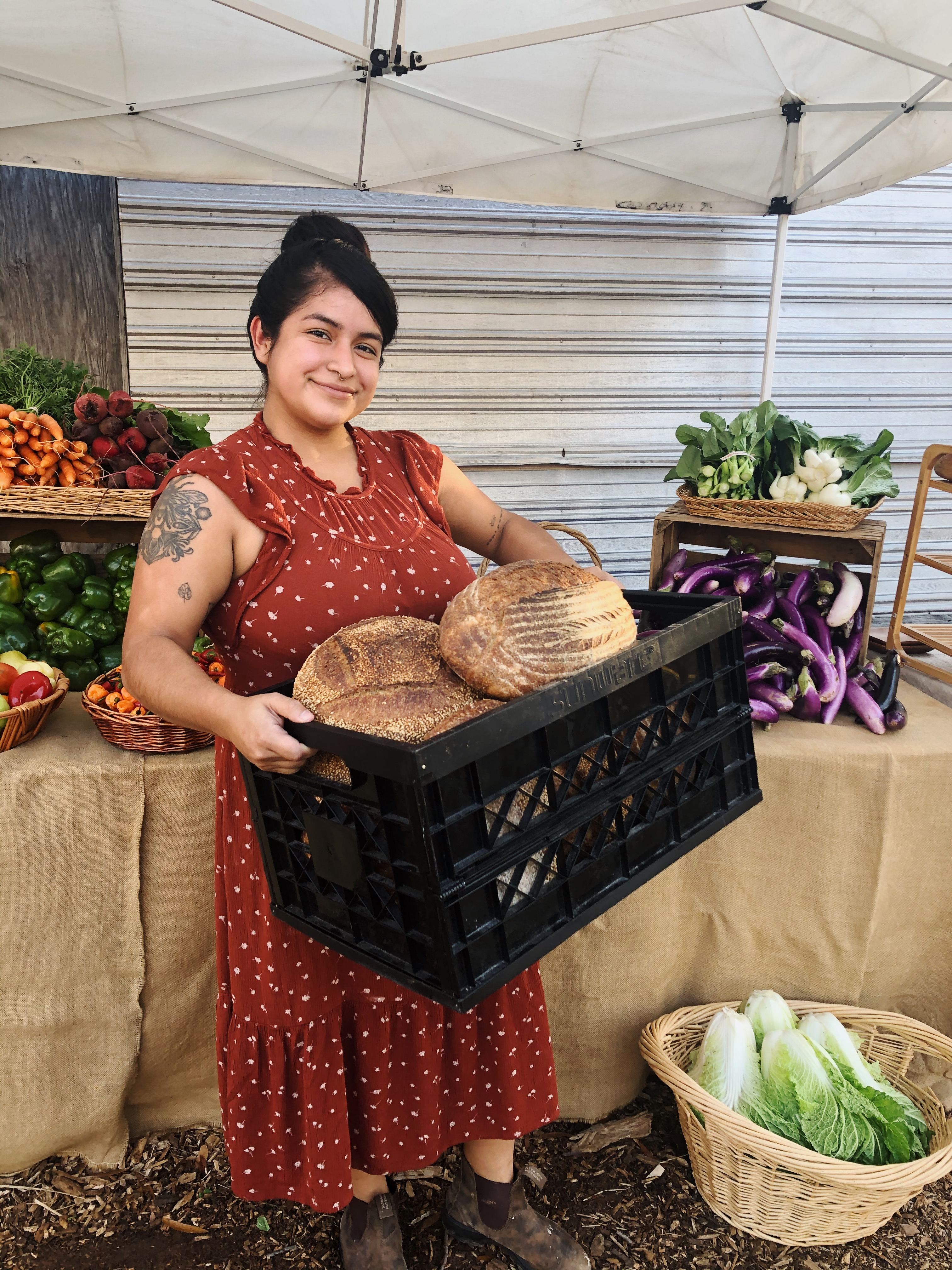 A photo of baker Betsy Gonzalez of Osono Bread whole a milk carton of freshly baked loaves of bread at the farmers market