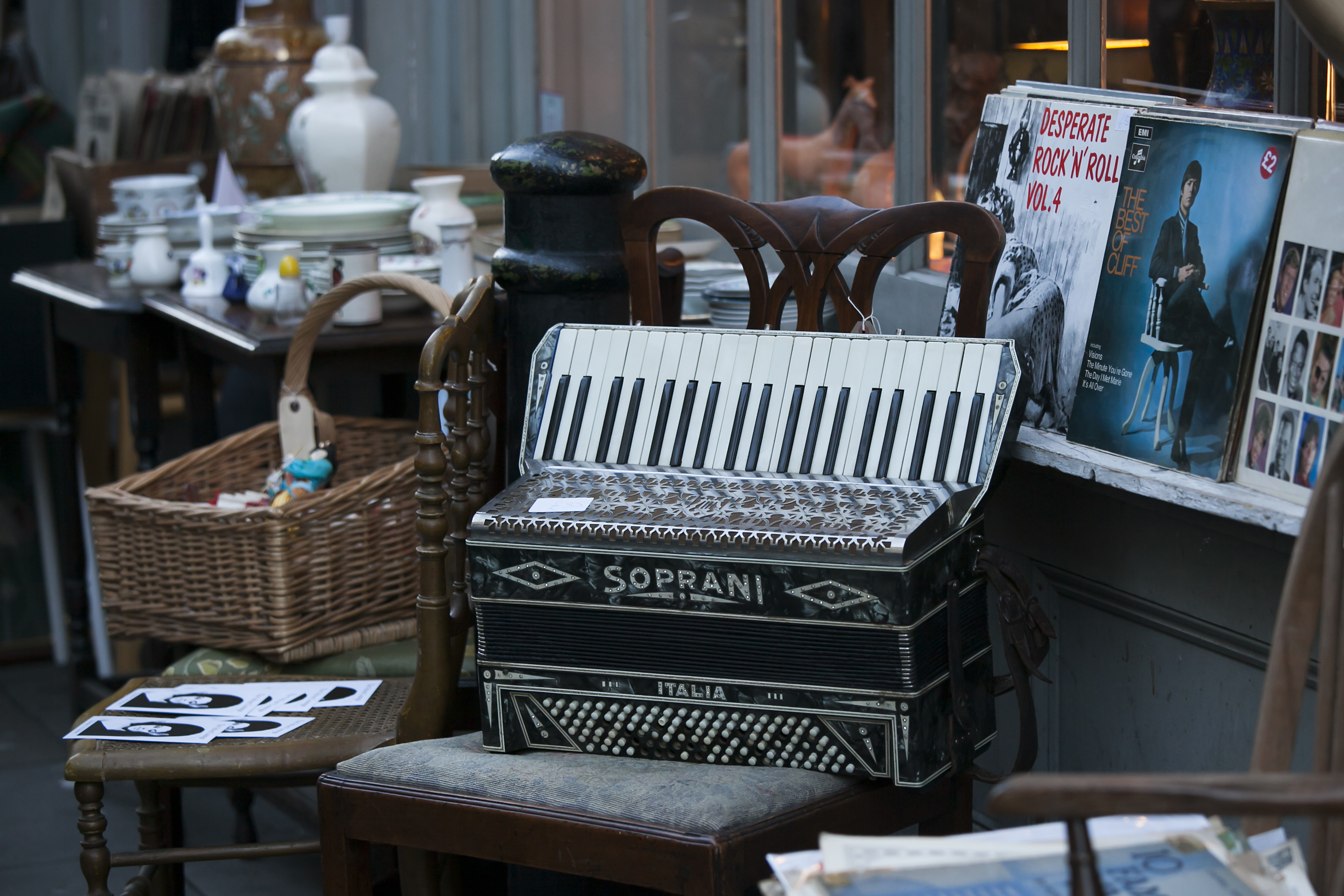 Photo of a setting in a flea market. There's an accordion on a chair in the foreground, surrounded by an old record album, a table, various dishes, and lamps.