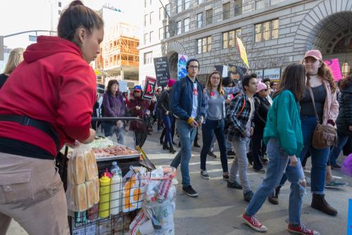 Street Vending in a red jacket on a sidewalk.