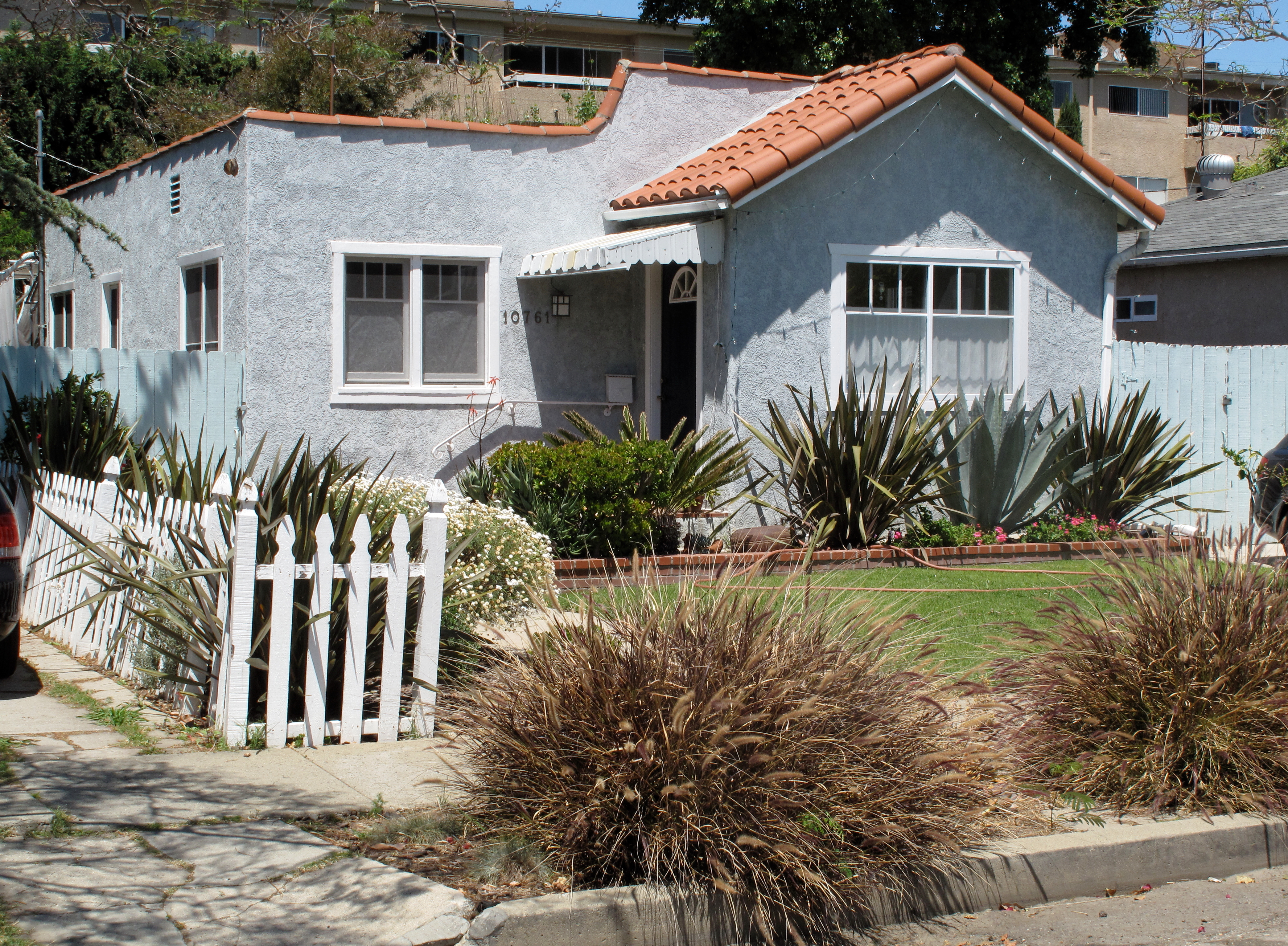 The exterior of a blue stucco house with a red tiled roof enclosed behind a white picket fence.