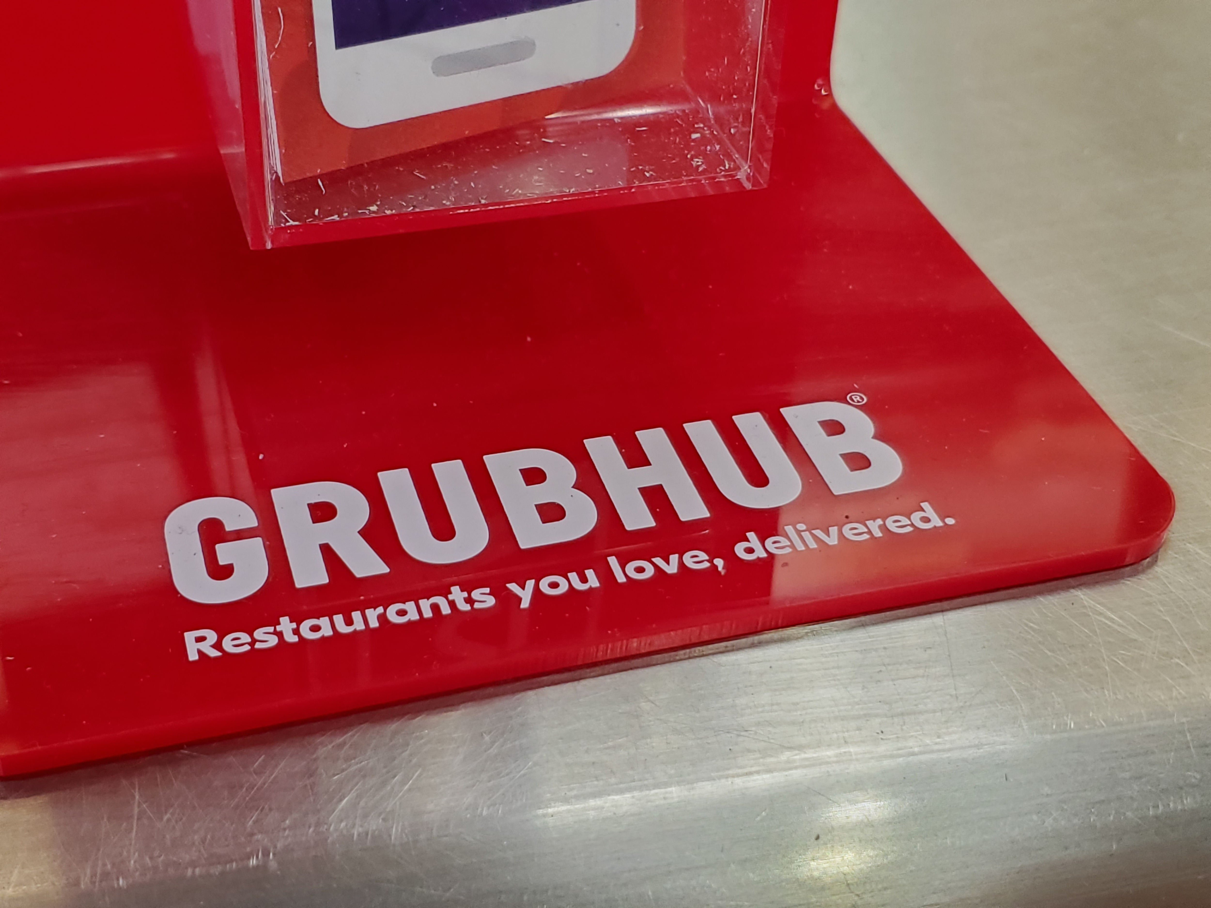 Close-up of logo for food delivery service Grubhub in a restaurant.