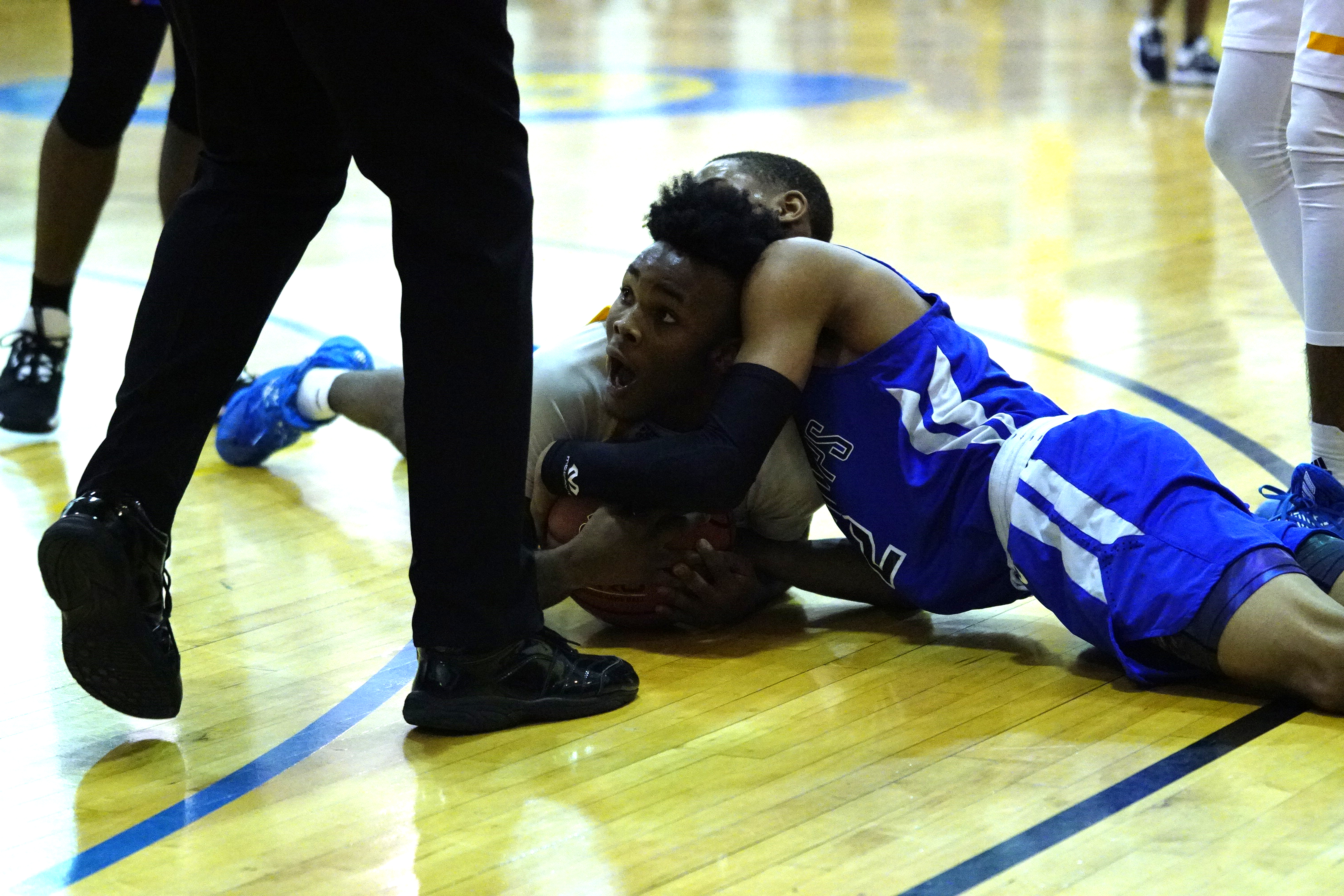 Dunbar's Damione Howard (5) battles Phillips' Davion Jordan (2) over a loose ball.