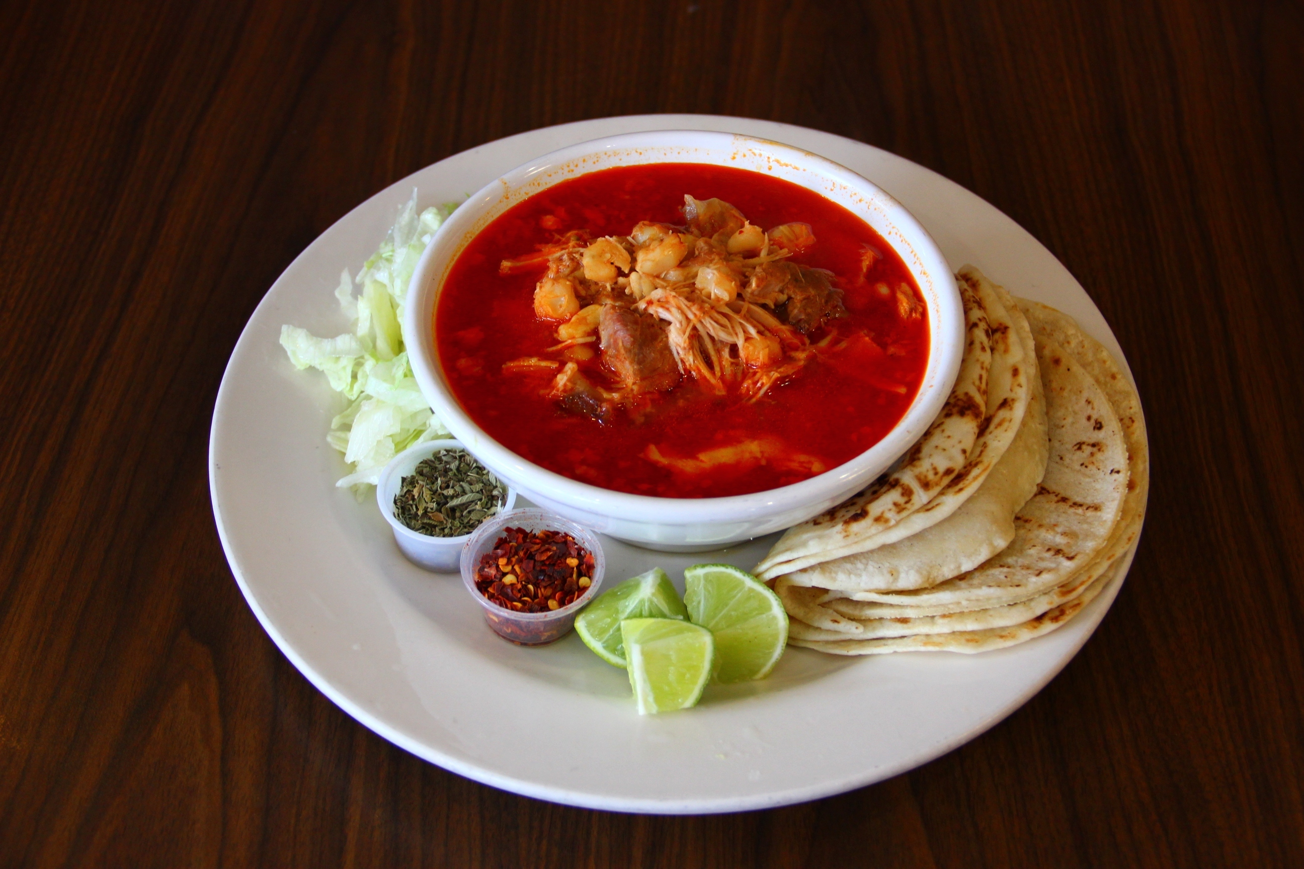 A view of a bowl of pozole, with tortillas, lime, and sauces on the side.