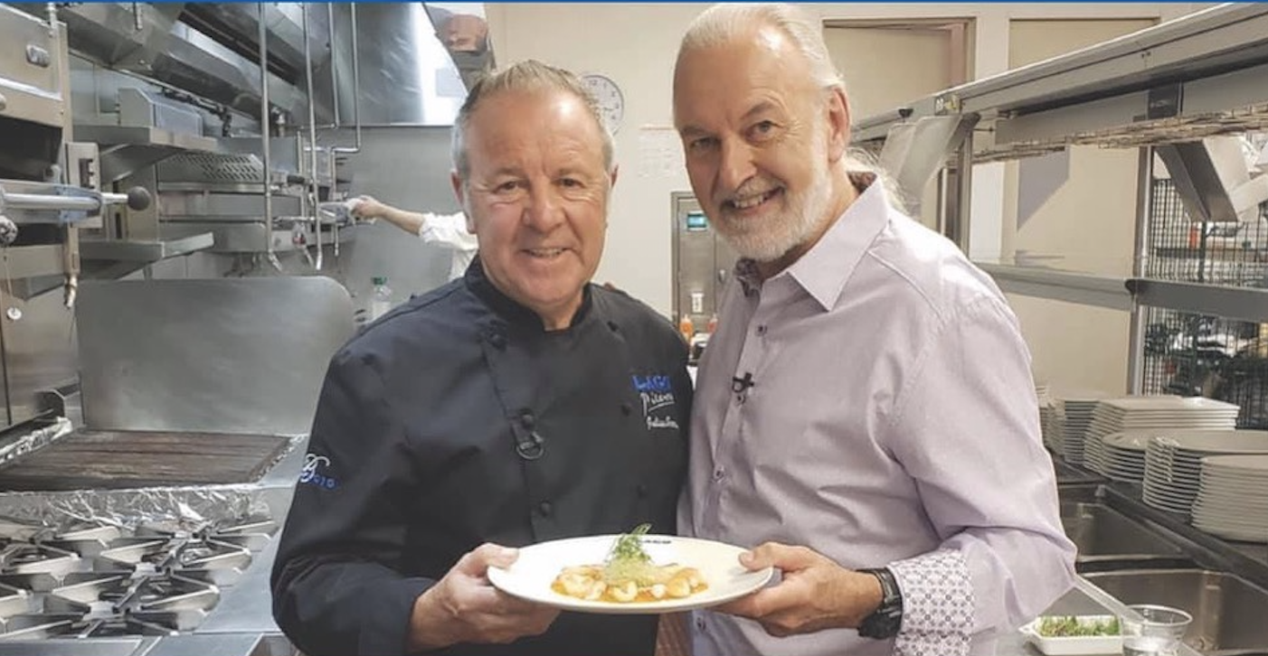 Two chefs hold a plate of food